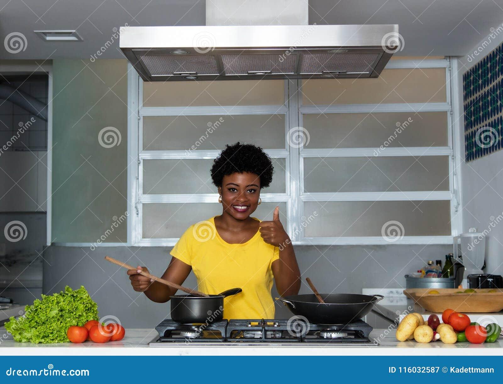 Mujer afroamericana que cocina en la cocina
