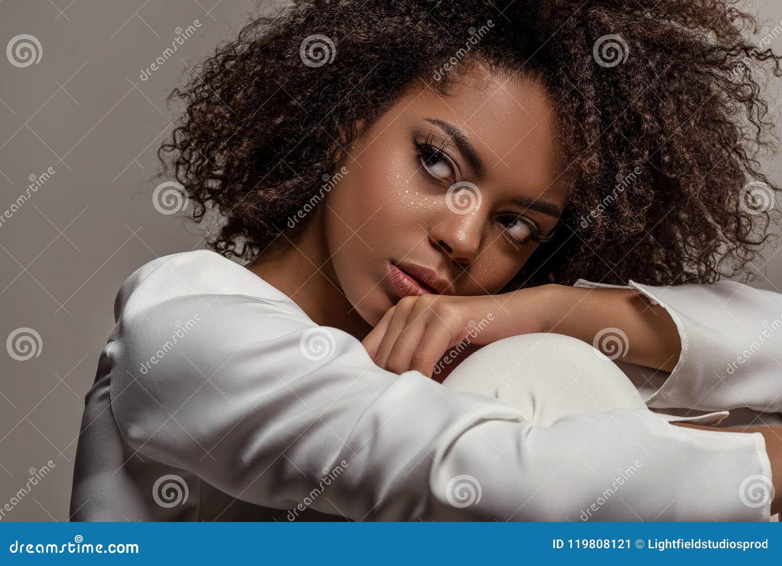Mujer afroamericana sensual joven en la camisa blanca que mira lejos