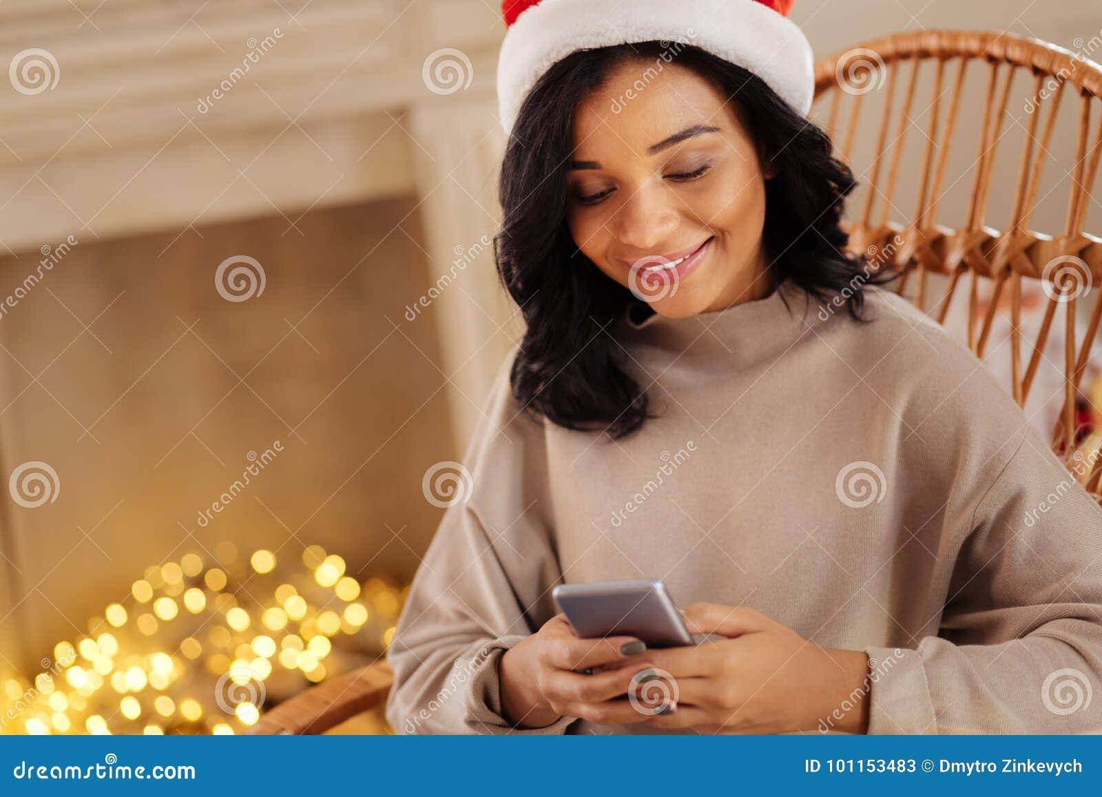 Envío de amor Mujer joven encantadora que se sienta en una mecedora y que  manda un SMS a su marido mientras que lleva un sombrero de Papá Noel 9ee15921c60