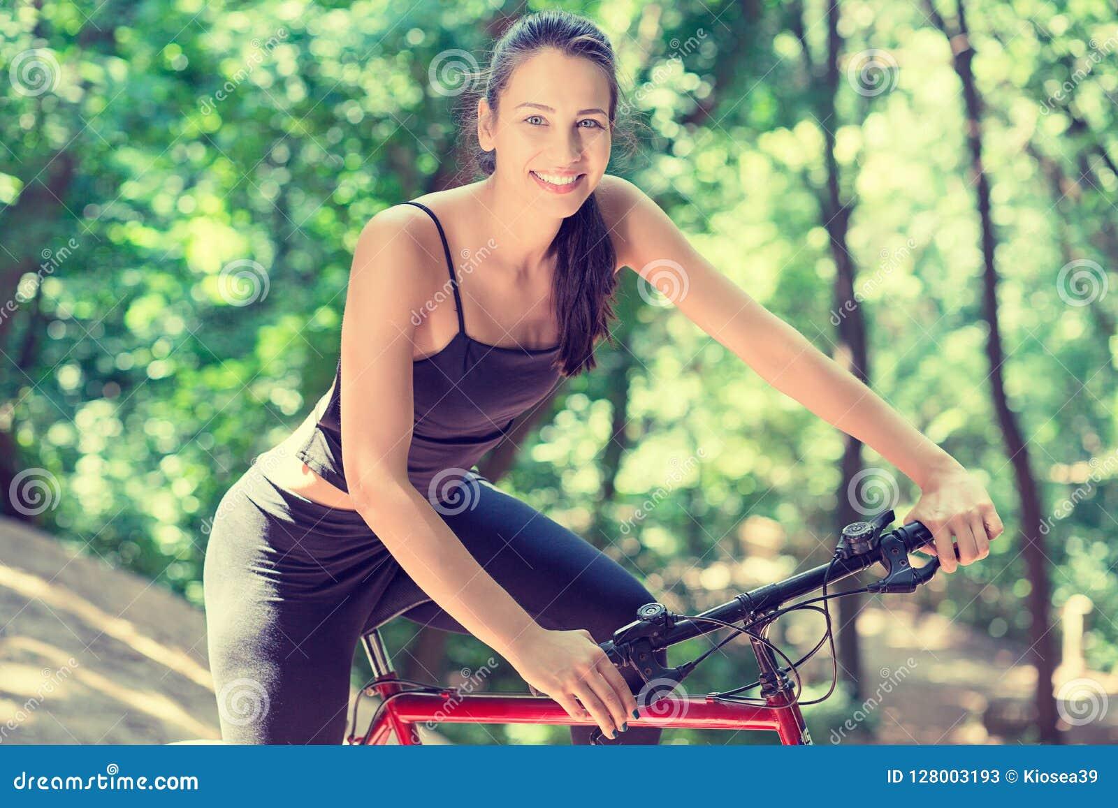 Mujer alegre con la bicicleta en parque