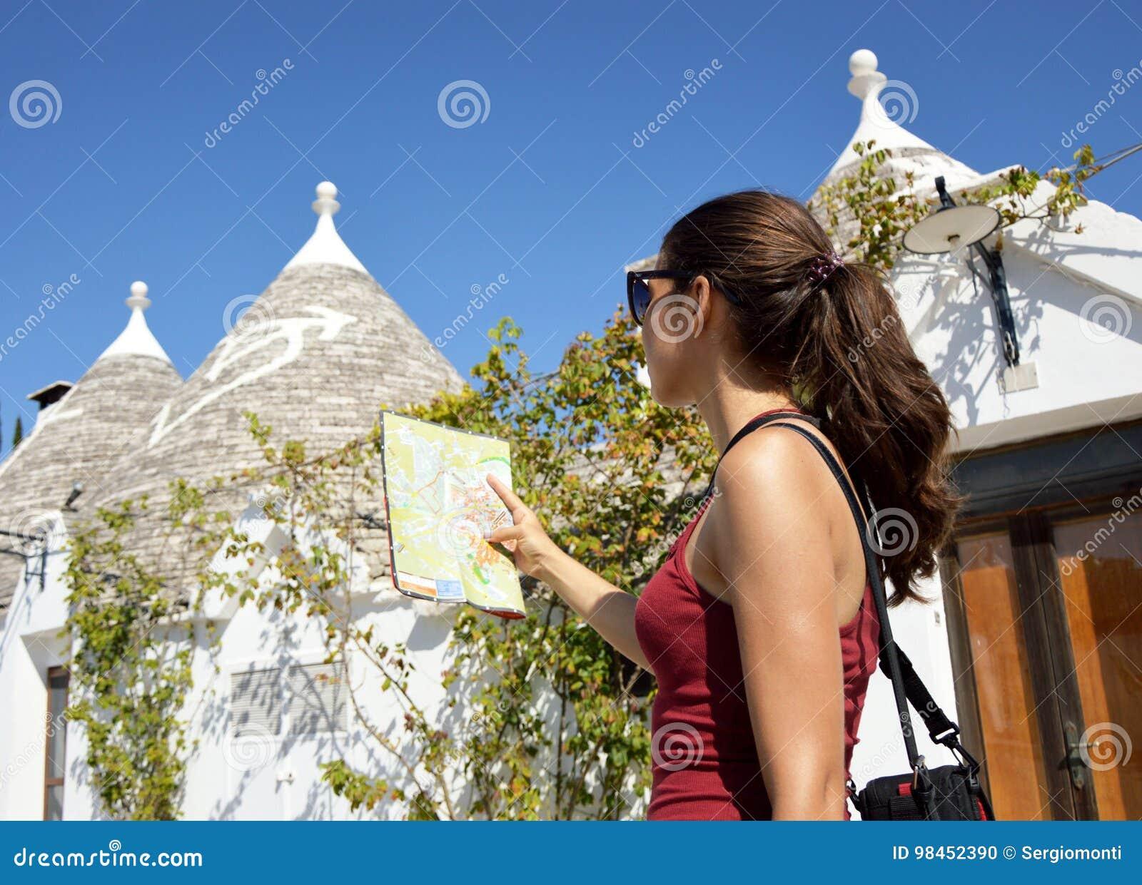 Mujer alegre con las gafas de sol y el pelo largo que buscan la dirección en mapa de ubicación mientras que viaja al extranjero,