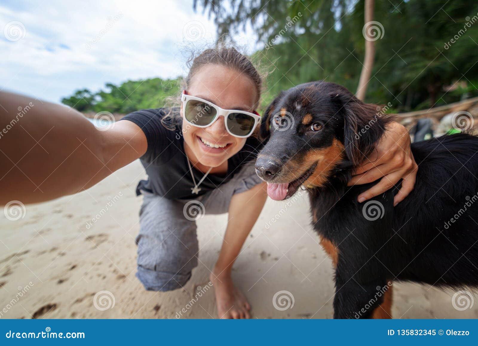 Mujer alegre feliz hermosa joven de la muchacha que se divierte que toma un selfie en un teléfono móvil con su perro en la playa