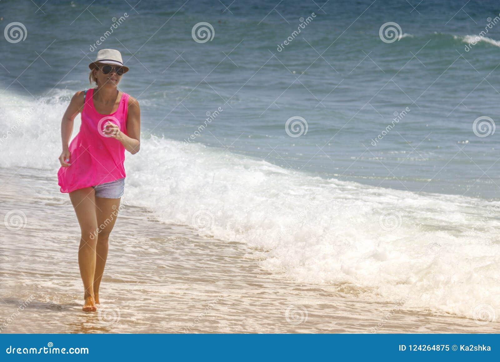 Mujer alegre feliz que corre a lo largo de la playa contra el océano