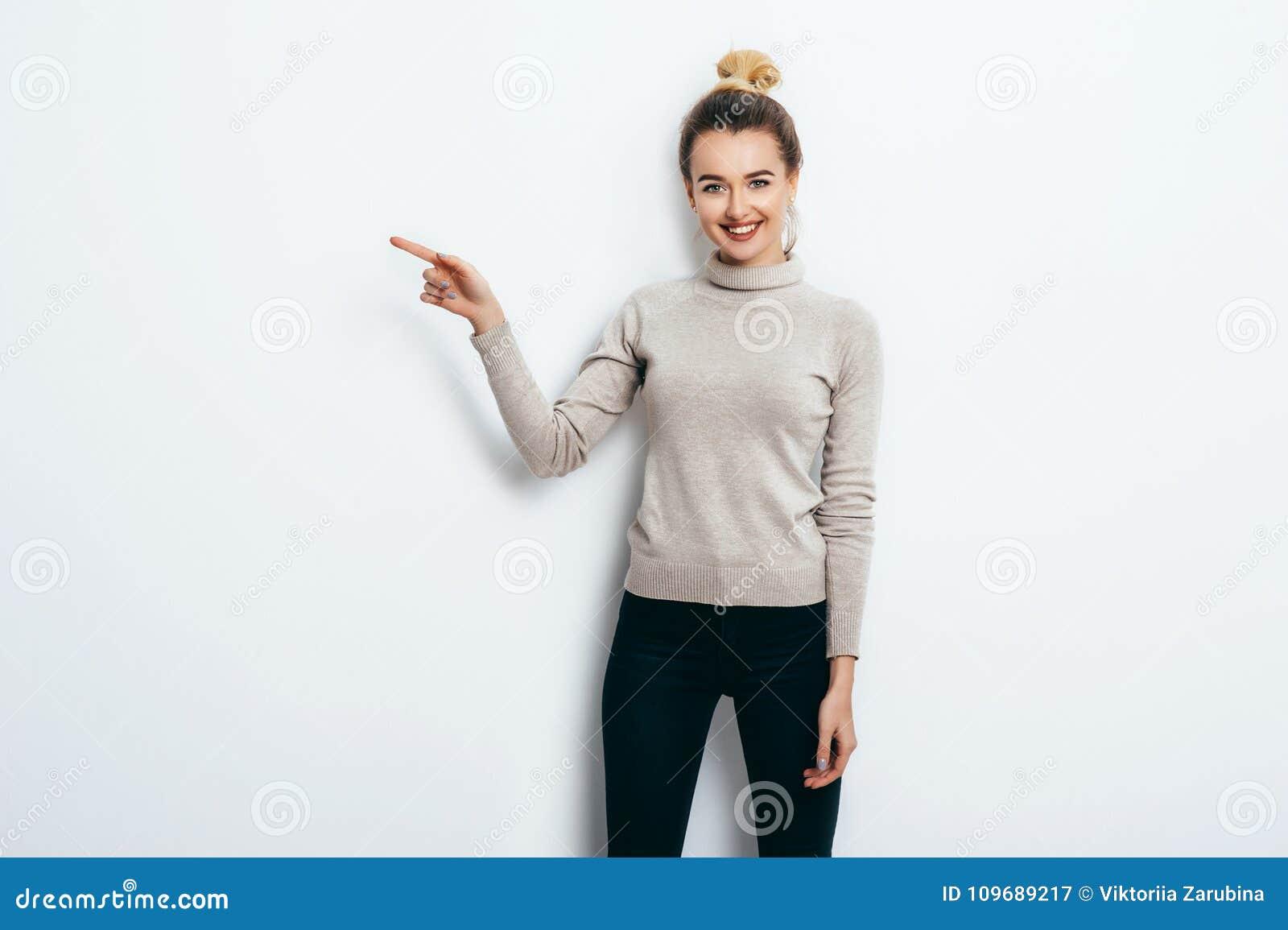 Mujer alegre hermosa joven con el bollo del pelo que lleva en vaqueros y el suéter que señala con el índice en espacio de la copi