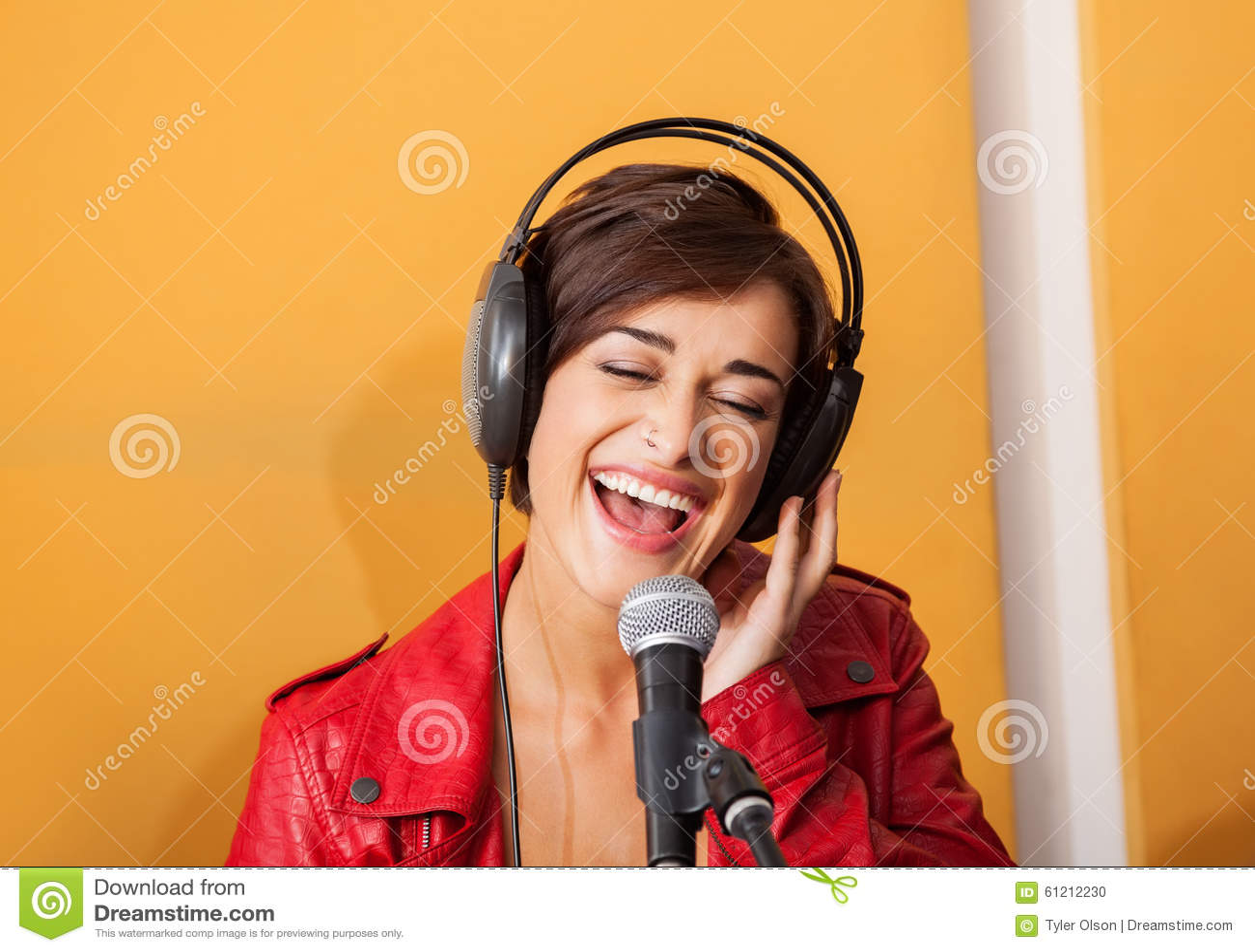 Mujer alegre que canta en el estudio de grabación