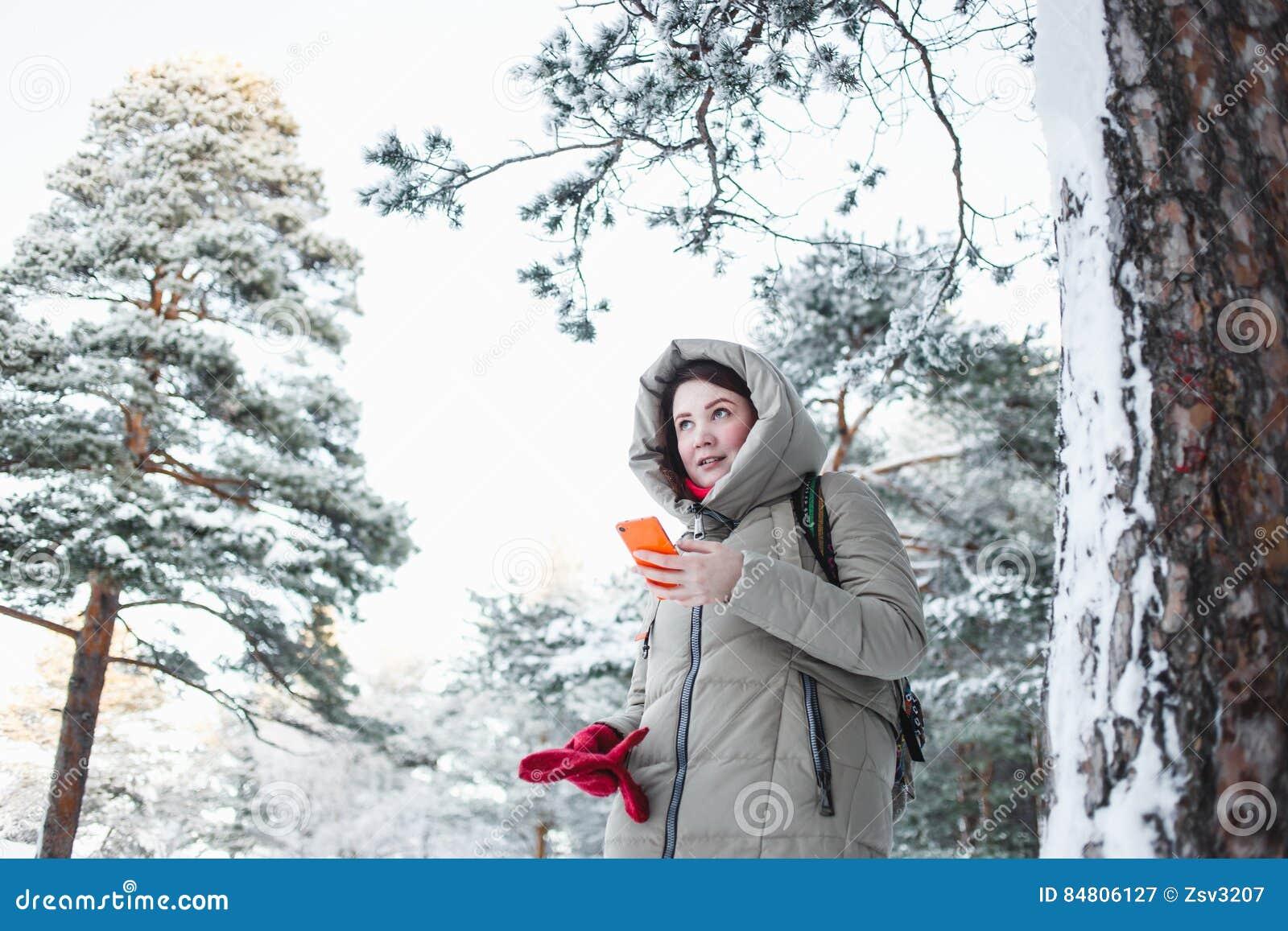 Mujer alegre que manda un SMS en smartphone anaranjado durante un viaje al bosque en invierno Modelo moreno que lleva la chaqueta