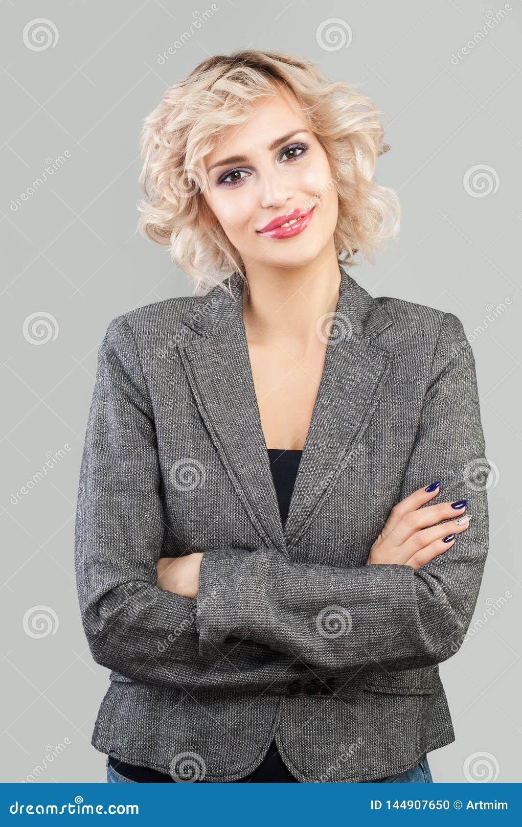 Mujer amistosa feliz que sonríe y que se coloca con el retrato cruzado de los brazos Empresaria elegante en retrato del traje