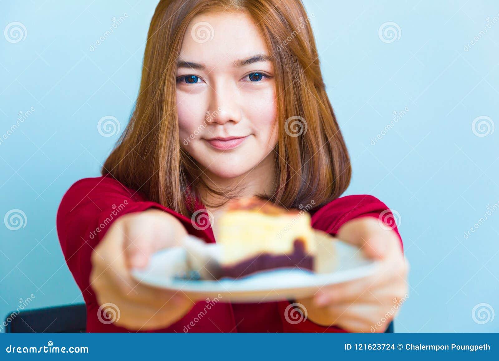 Mujer asiática atractiva joven feliz que sonríe y que da un pedazo o