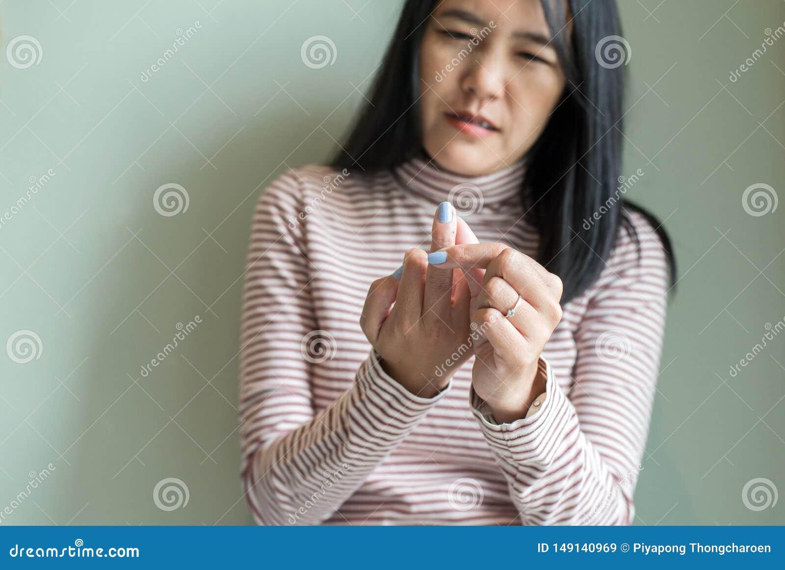 Mujer asi?tica con beriberi a mano o el finger, enfermedad que causa la inflamaci?n de los nervios