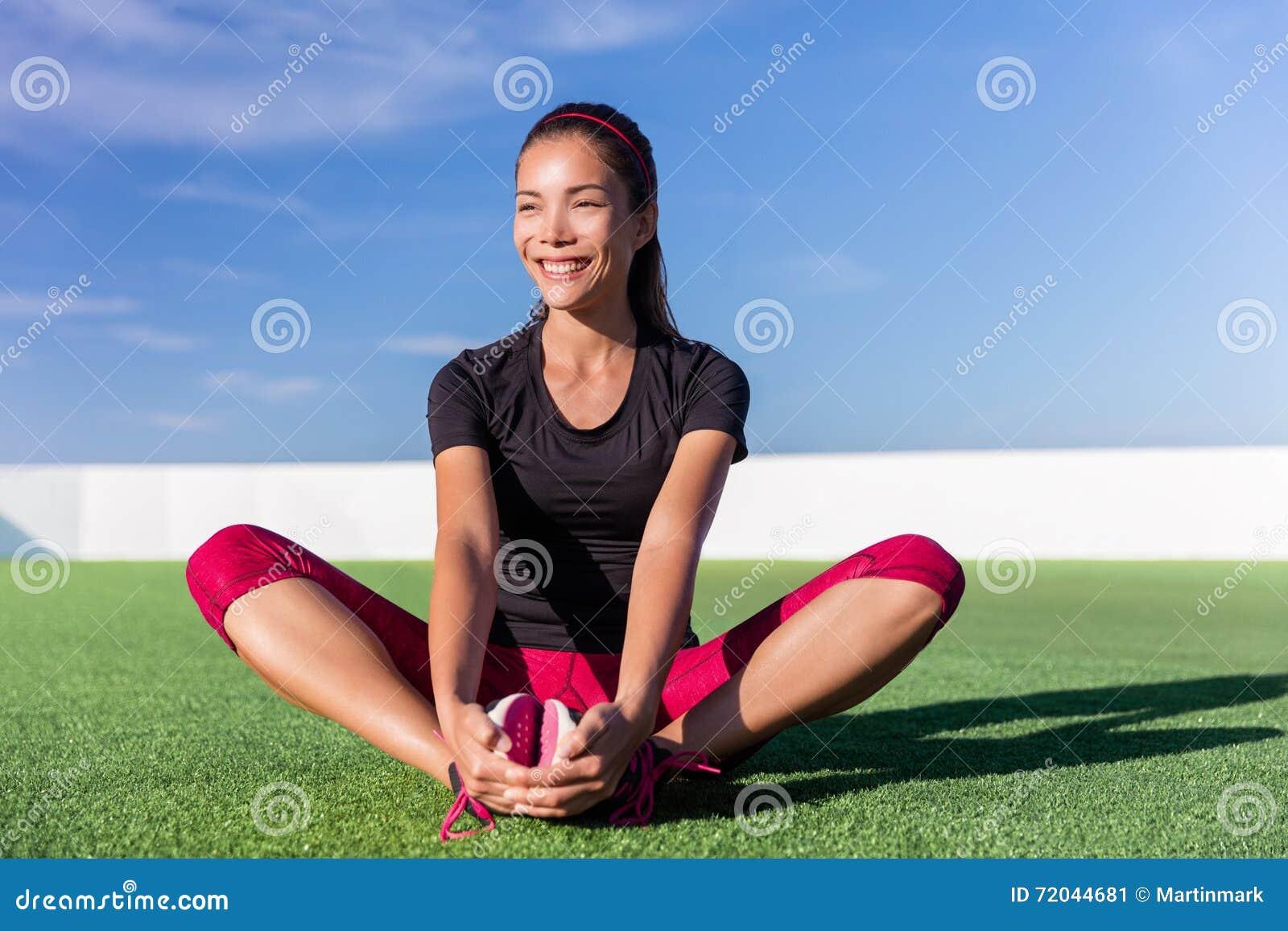 Mujer asiática de la aptitud feliz que estira las piernas en parque