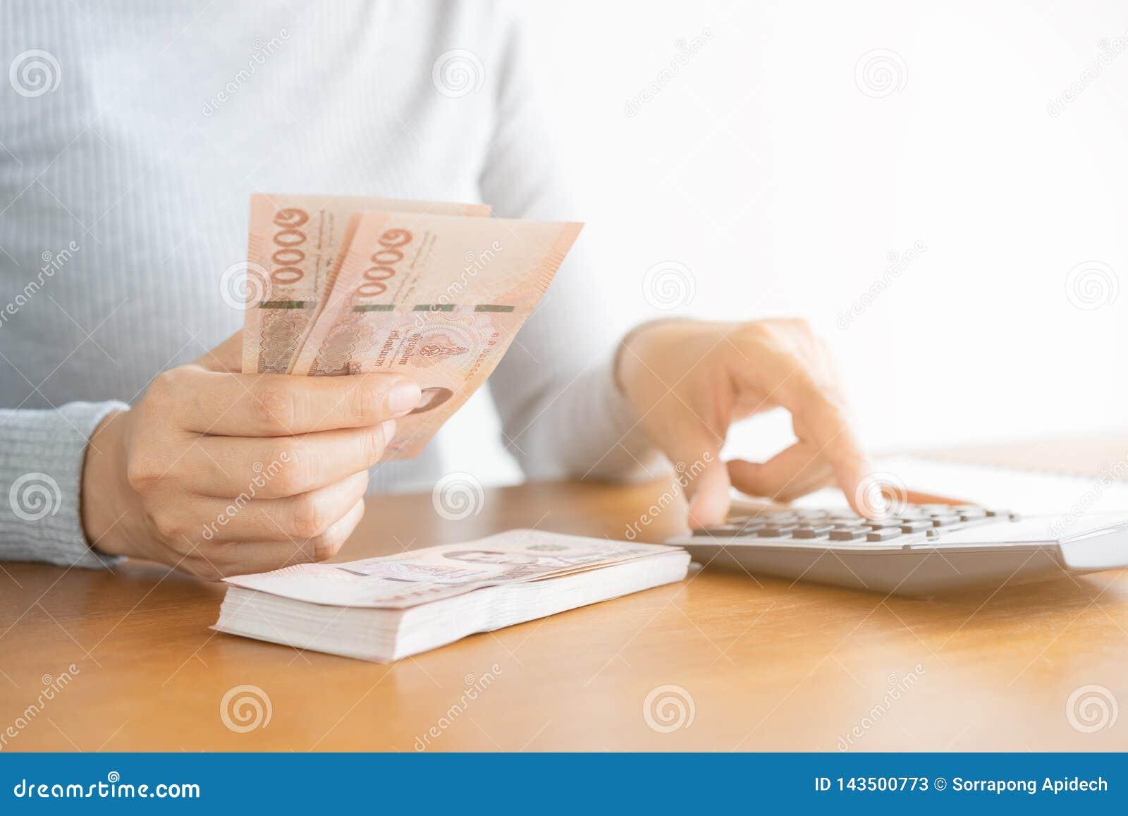 Mujer asiática de la mano del primer usando la calculadora que cuenta y contar el dinero en hogar