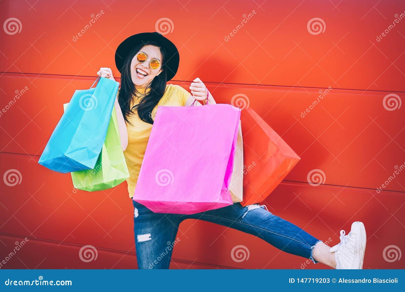 Mujer asiática de la moda feliz que hace compras en el centro de la alameda - muchacha china joven que se divierte que compra nue