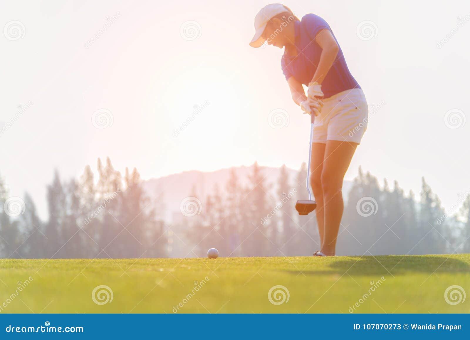 Mujer asiática del golfista que pone la pelota de golf en el golf verde en tiempo determinado de la tarde del sol