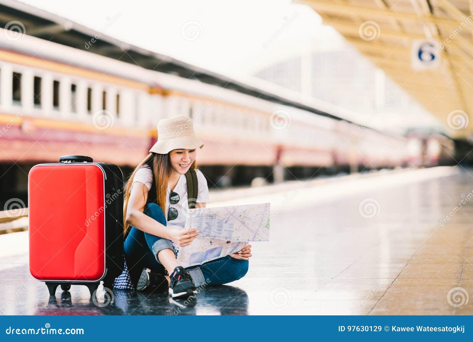 Mujer asiática del viajero de la mochila que usa el mapa local genérico, localizando solamente en la plataforma de la estación de