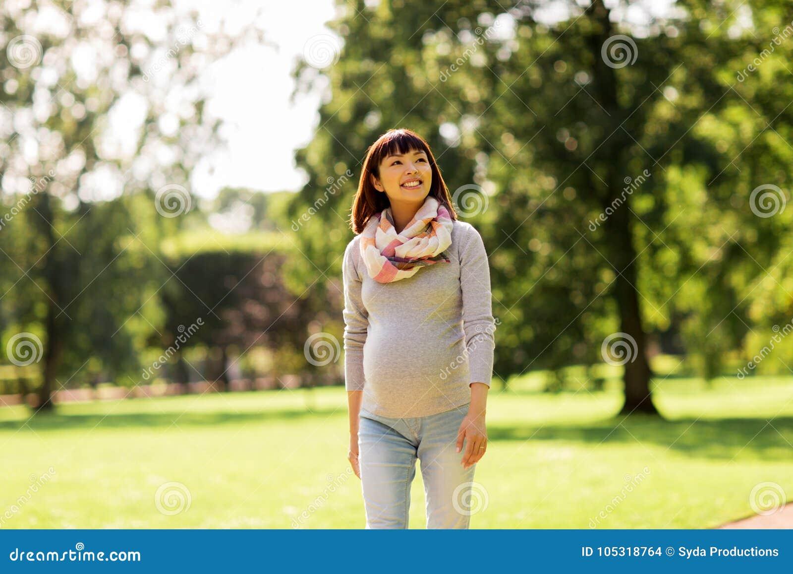 Mujer asiática embarazada feliz que camina en el parque