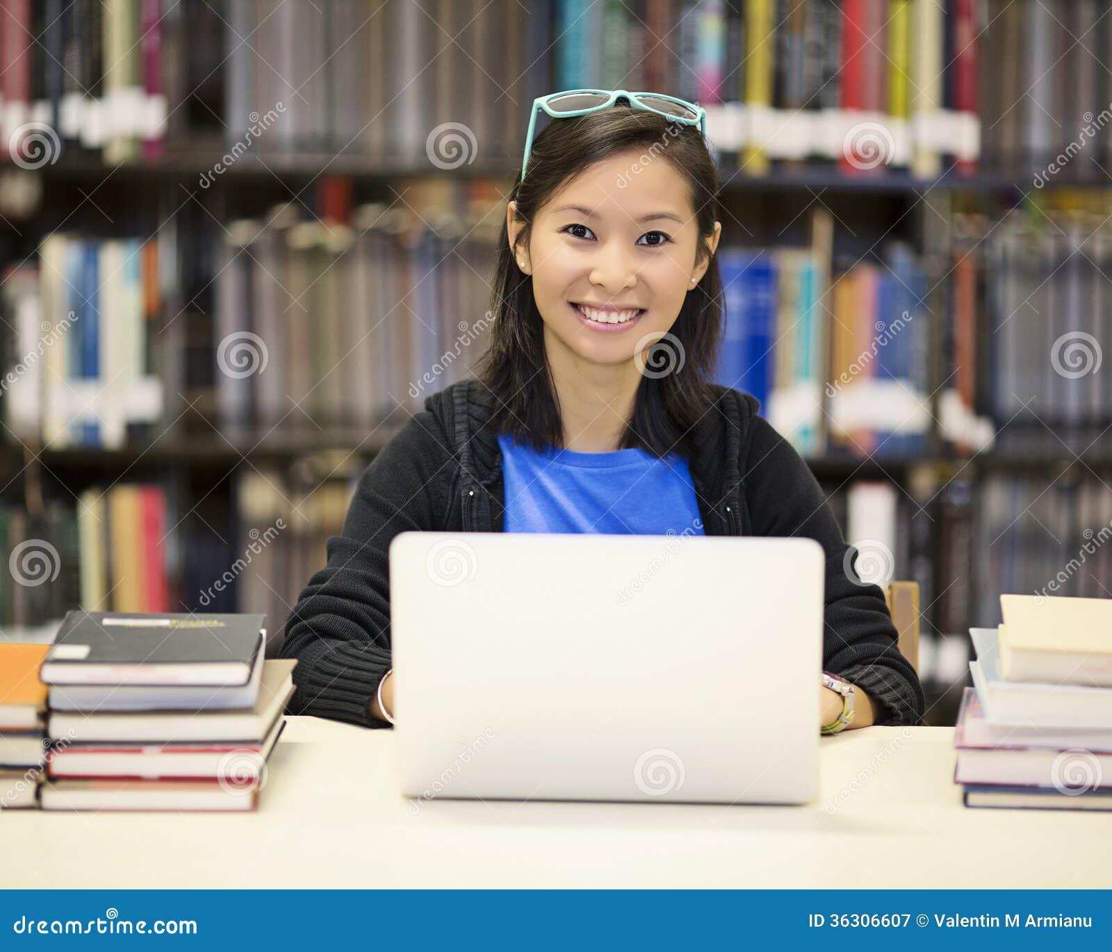 Mujer asiática en biblioteca con el ordenador portátil
