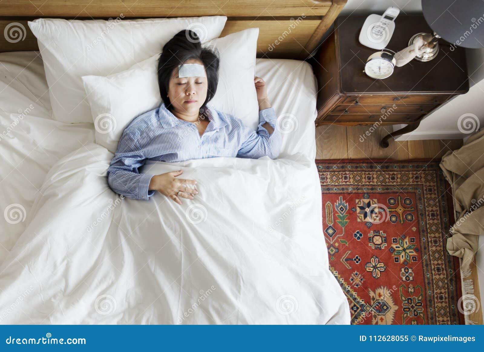 Mujer asiática enferma con fiebre que duerme en la cama