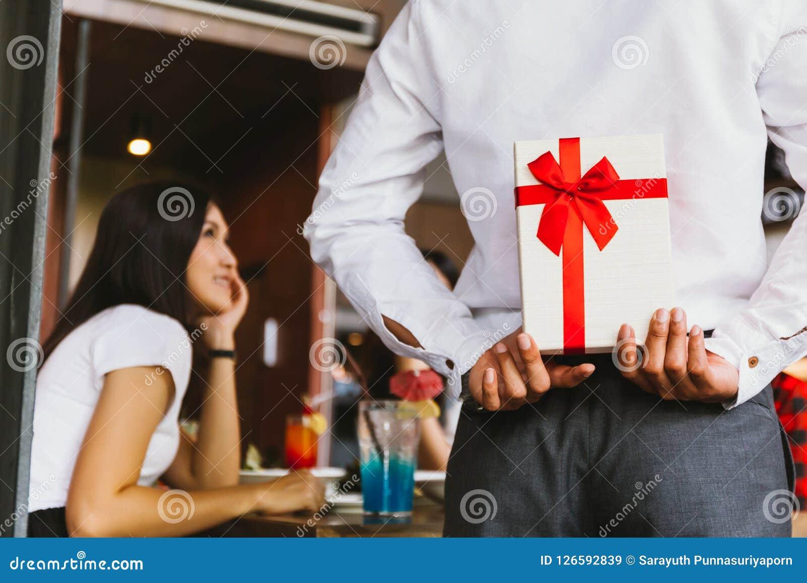 Mujer asiática esperada recibir una caja de regalo del presente de la sorpresa de hombre como par romántico para la celebración o