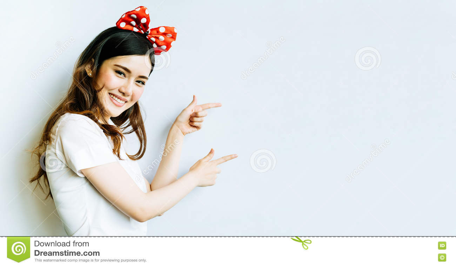 Mujer asiática hermosa de la universidad o del estudiante universitario que lleva la venda divertida del arco, señalando en el es