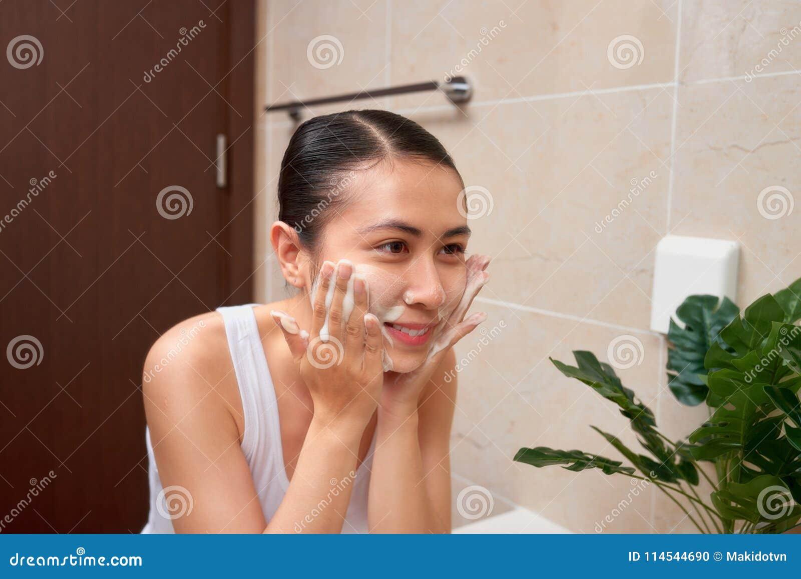 Mujer asiática hermosa joven que se lava la cara con las manos por el jabón