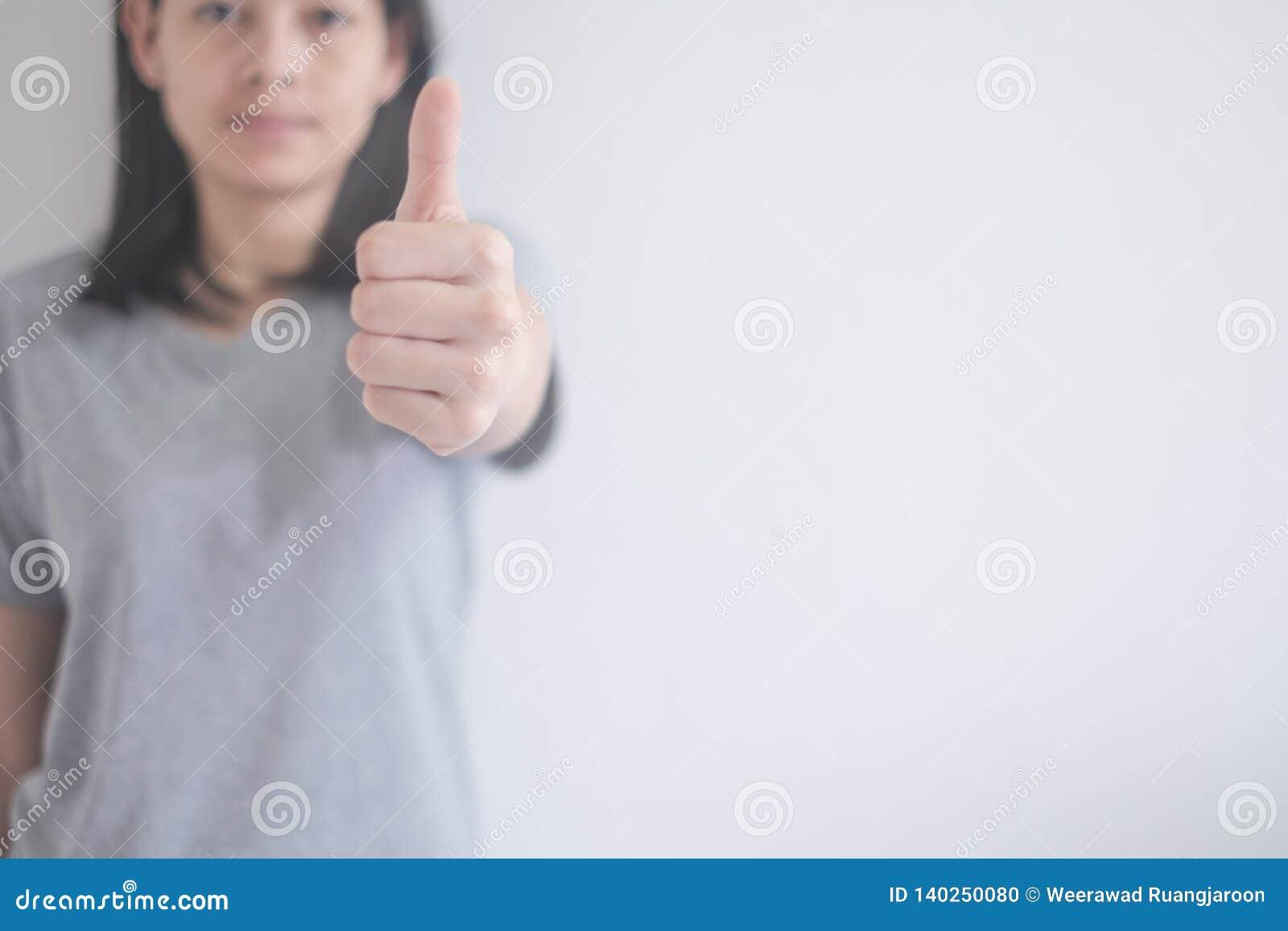 Mujer asiática hermosa que muestra los pulgares para arriba en un fondo blanco con el espacio de la copia