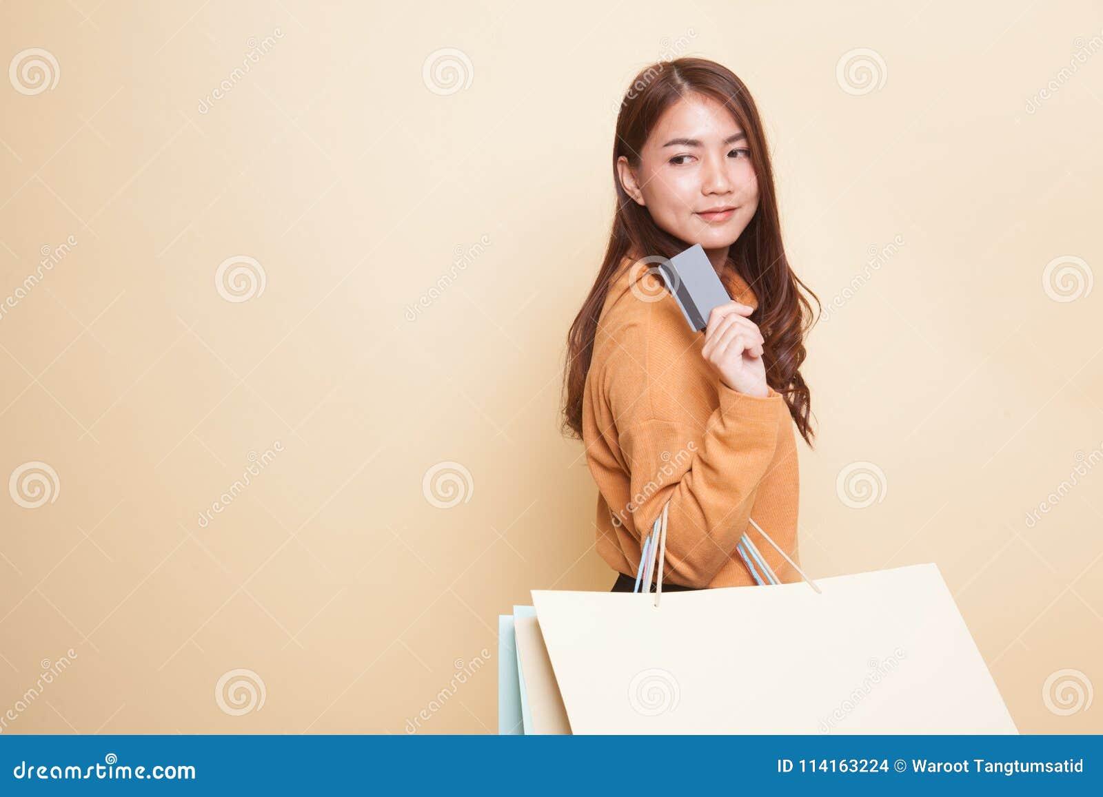 Mujer asiática joven con el panier y la tarjeta en blanco