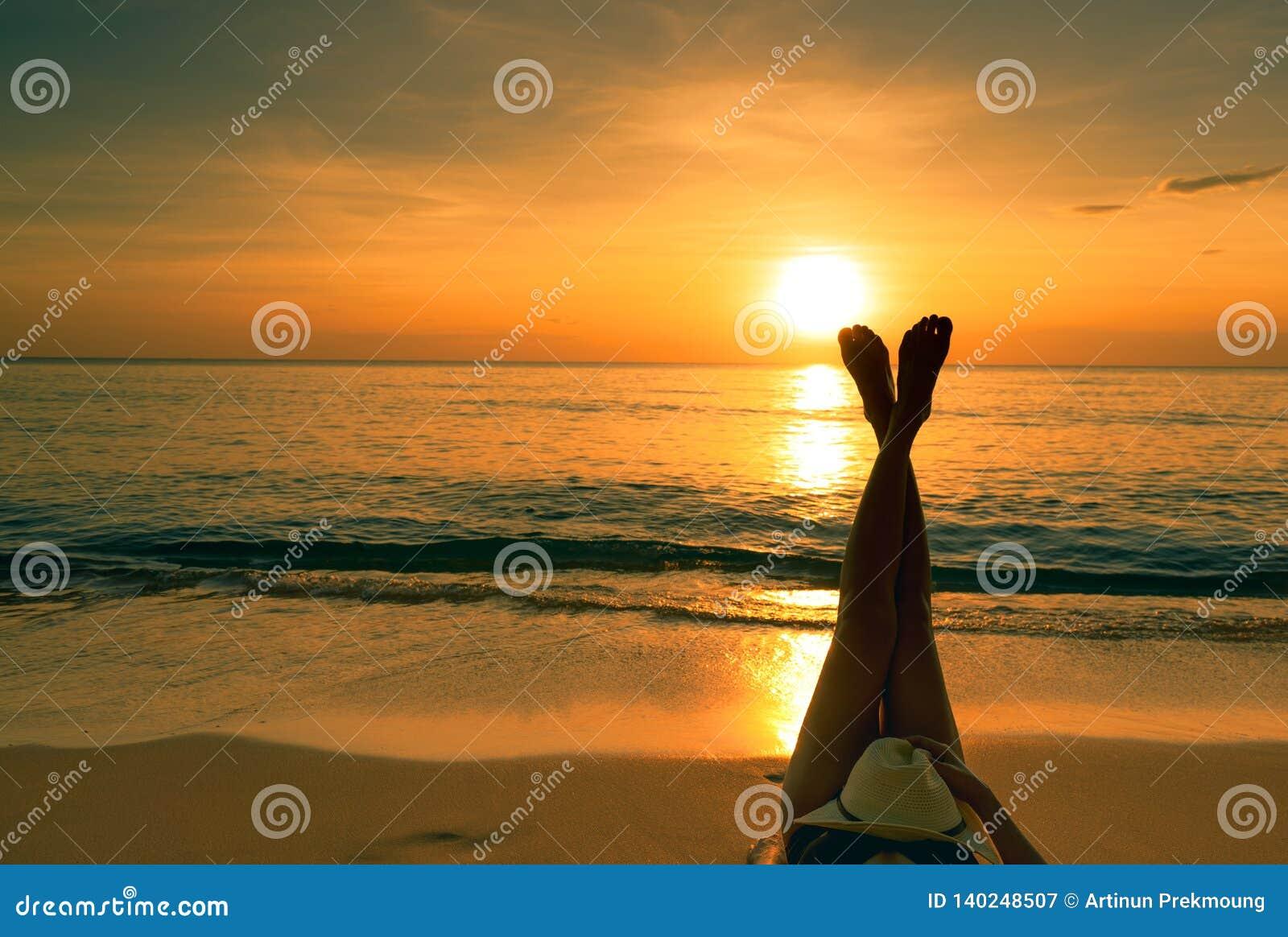 Mujer asiática joven con el sombrero que se relaja en la playa en la puesta del sol Muchacha que miente en la playa de la arena P