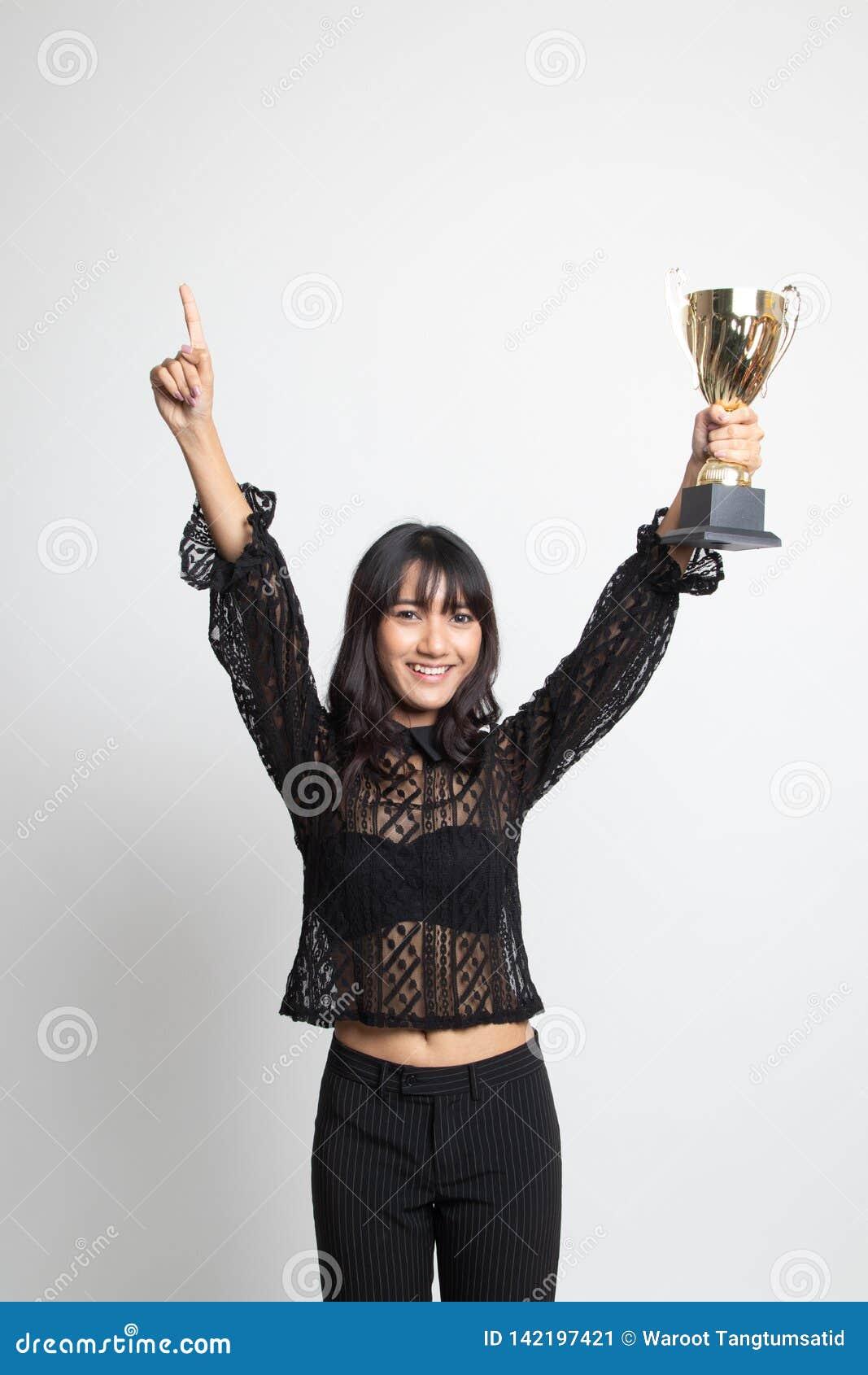 Mujer asiática joven del ganador acertado del número uno que sostiene un trofeo