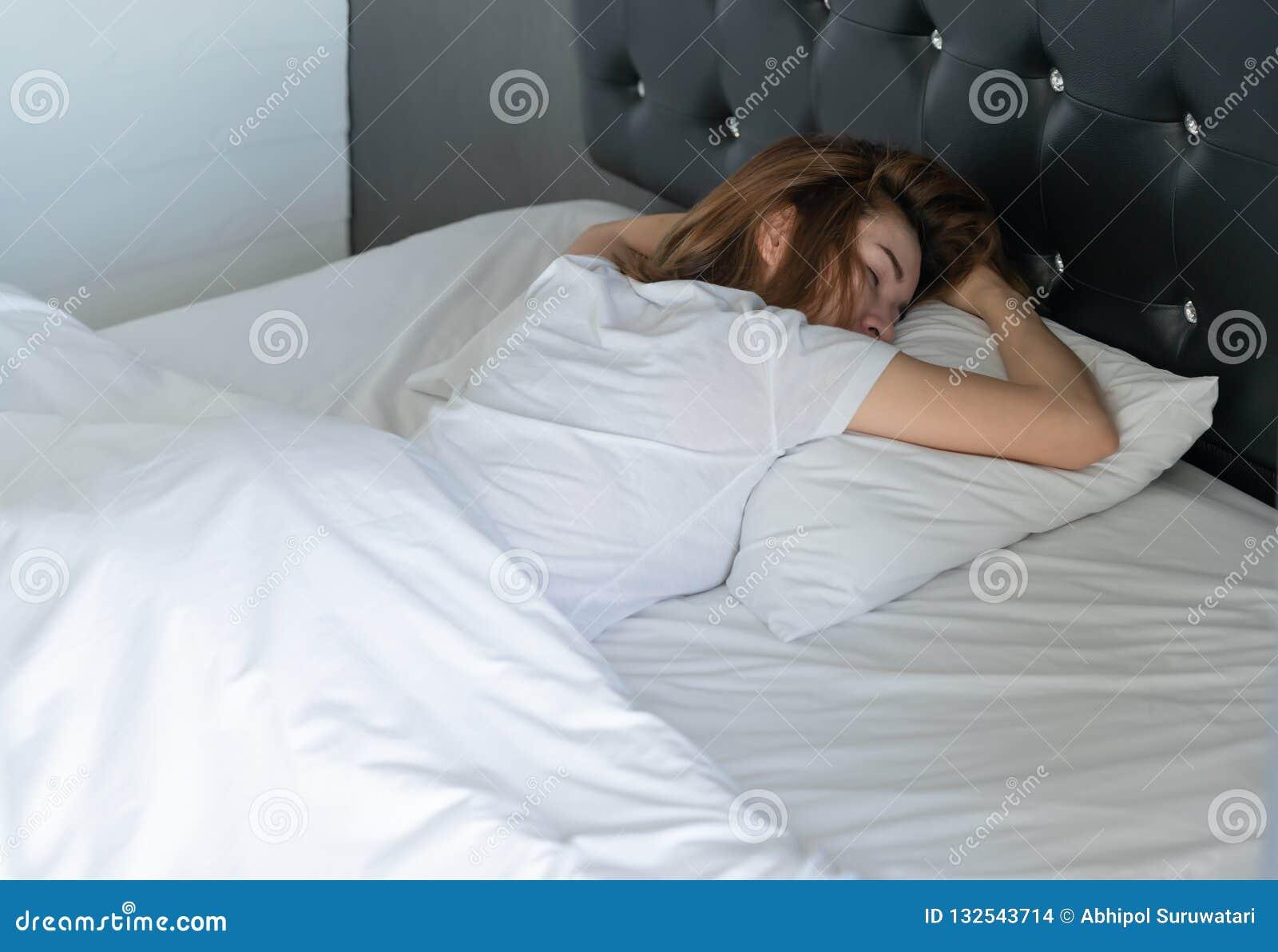 Mujer asiática joven hermosa en dormir casual blanco en la cama en casa mentira de la mujer en su estómago Alto ángulo sobre cuid