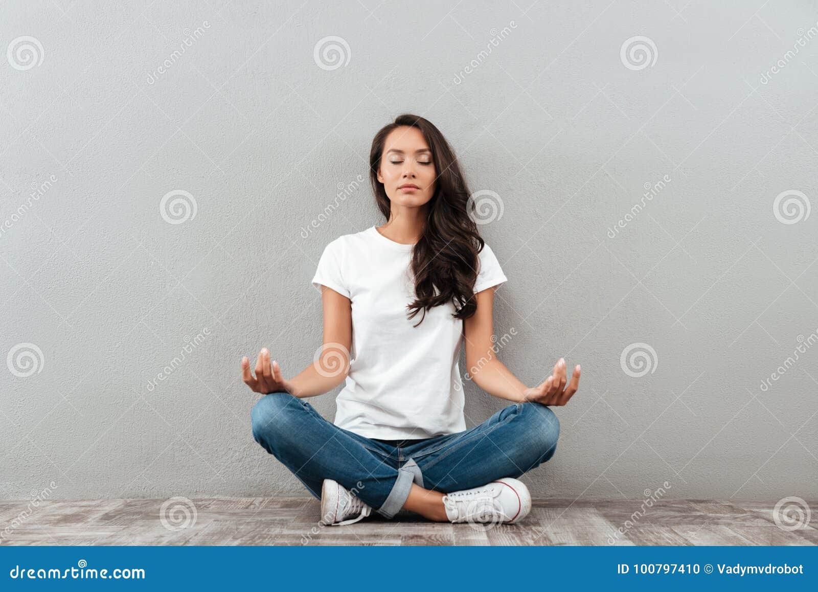 Mujer asiática joven hermosa que se sienta en la posición y meditar de la yoga