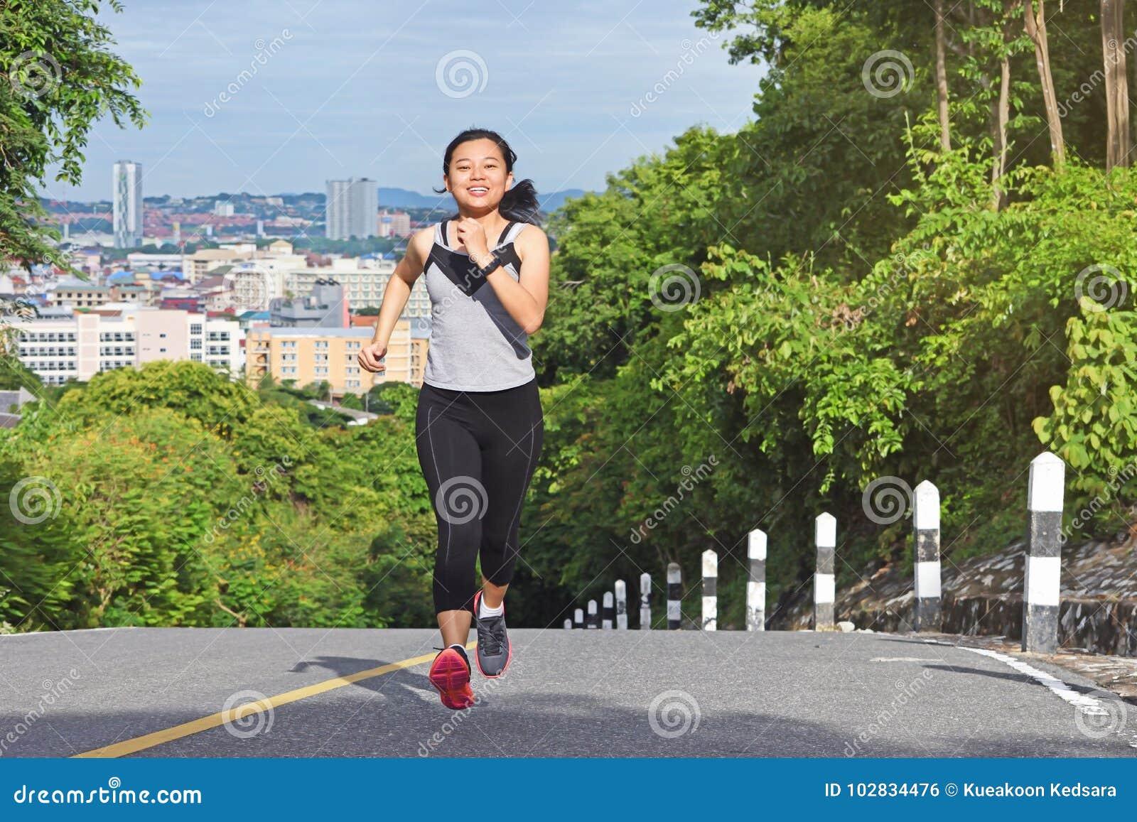 Mujer asiática joven que activa en el funcionamiento feliz sonriente del parque