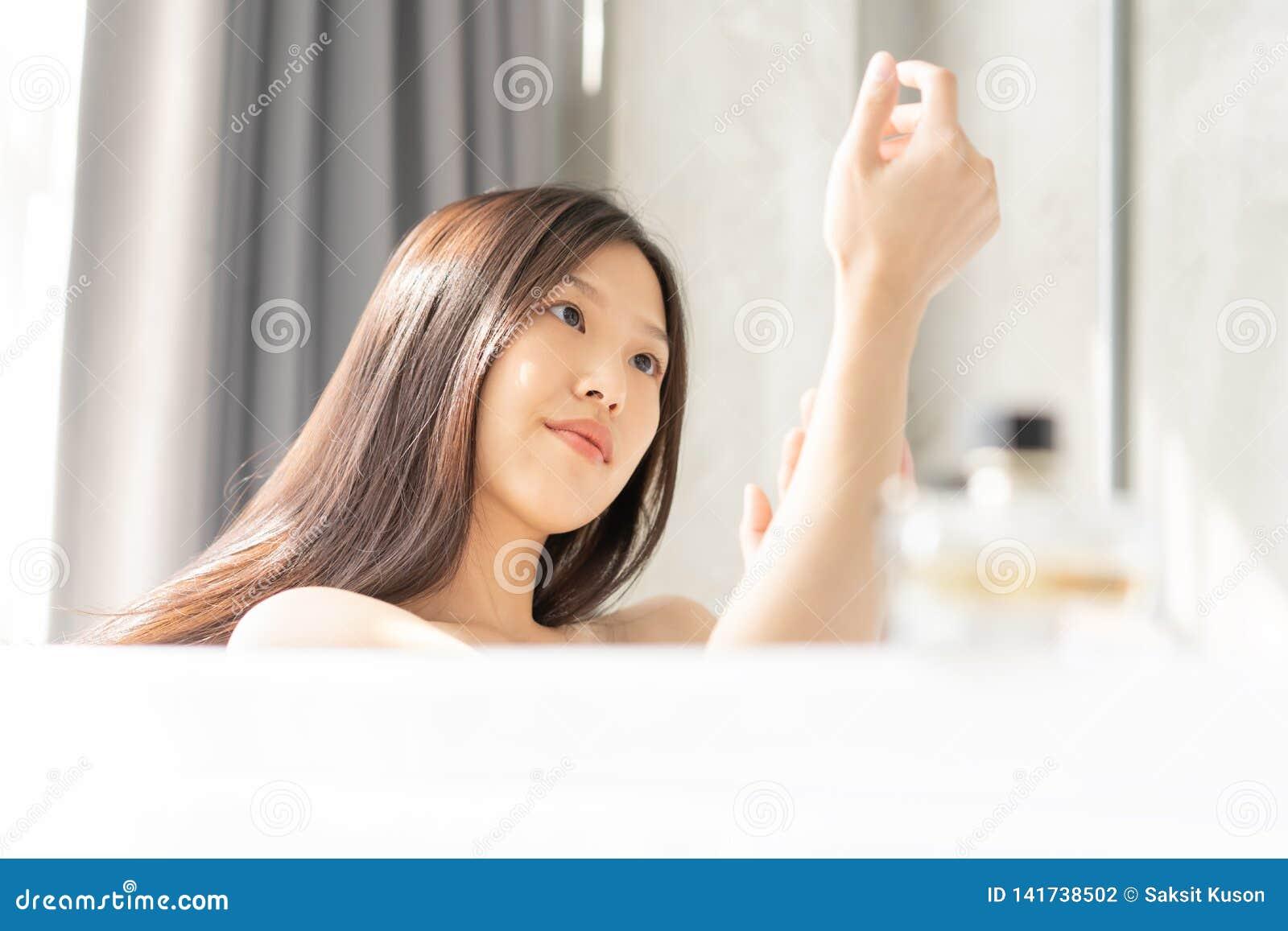 Mujer asiática joven que se relaja en un baño