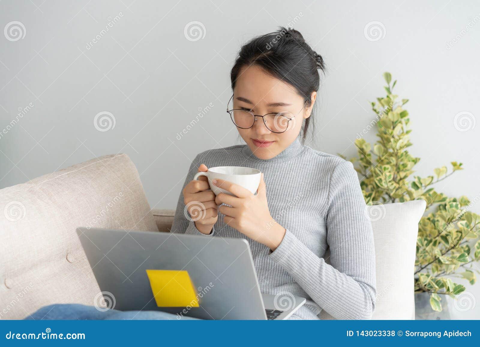 Mujer asiática joven que trabaja en el ordenador portátil en el escritorio de Ministerio del Interior y gozando de la taza de caf