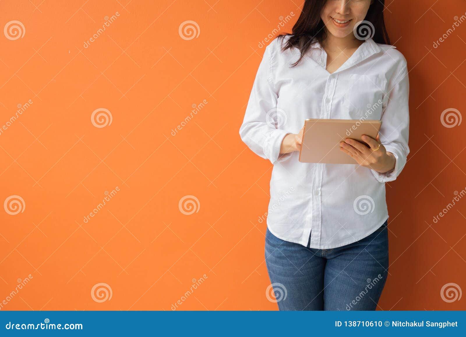 Mujer asiática joven que usa la tableta, smartphone, teléfono celular en fondo anaranjado aislado