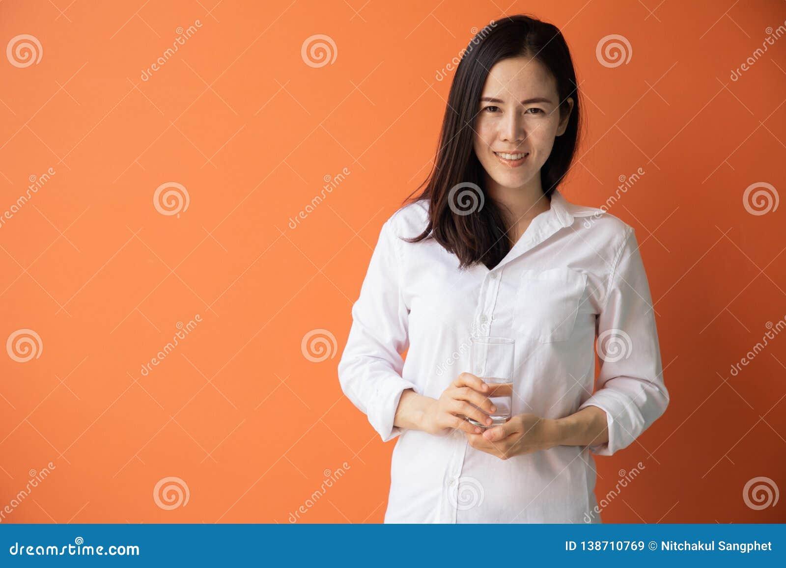 Mujer asiática joven sonriente que sostiene los vasos de agua en fondo anaranjado aislado