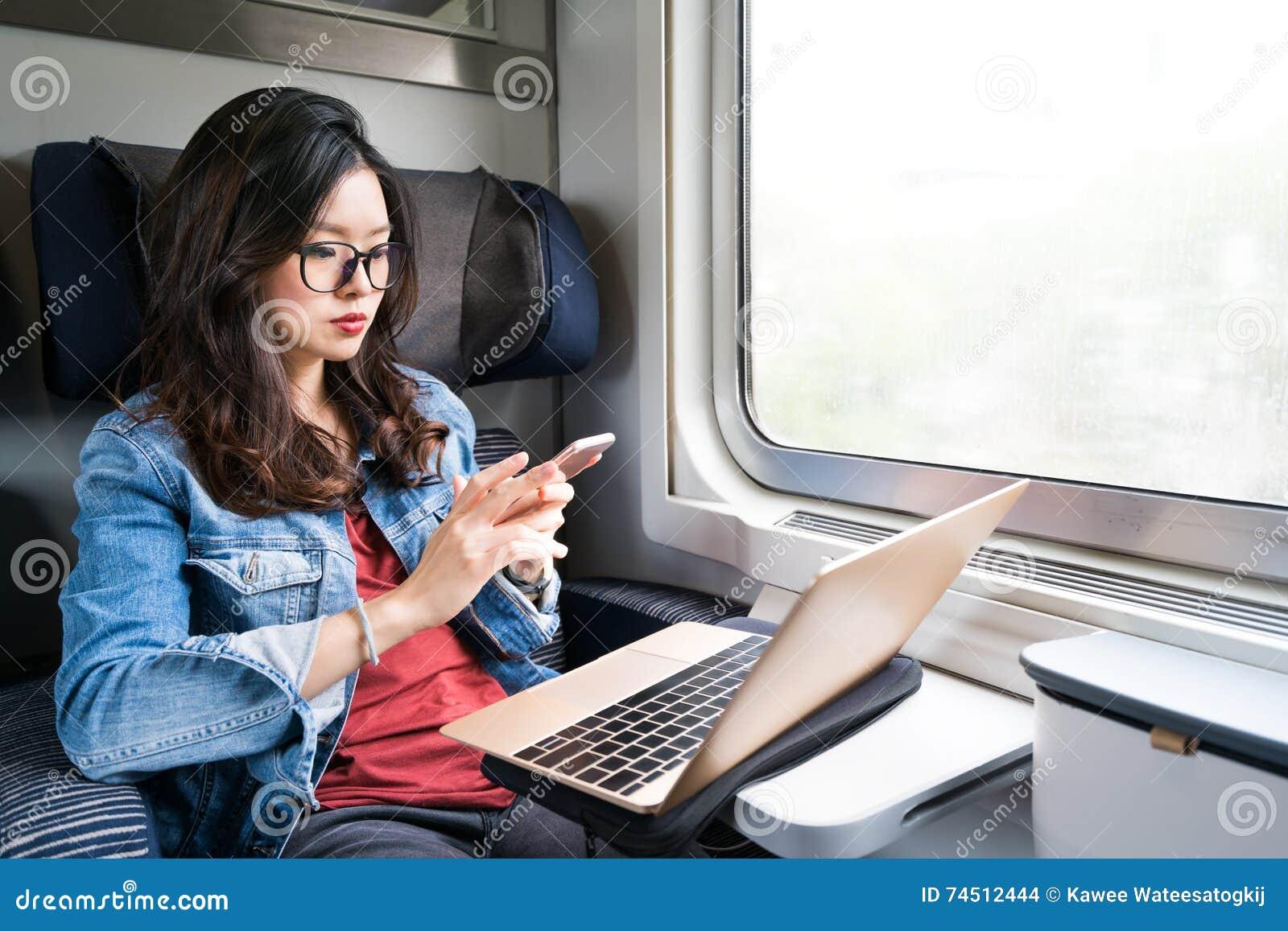 Mujer asiática linda que usa smartphone y el ordenador portátil en el tren, espacio de la copia en concepto de la ventana, del vi