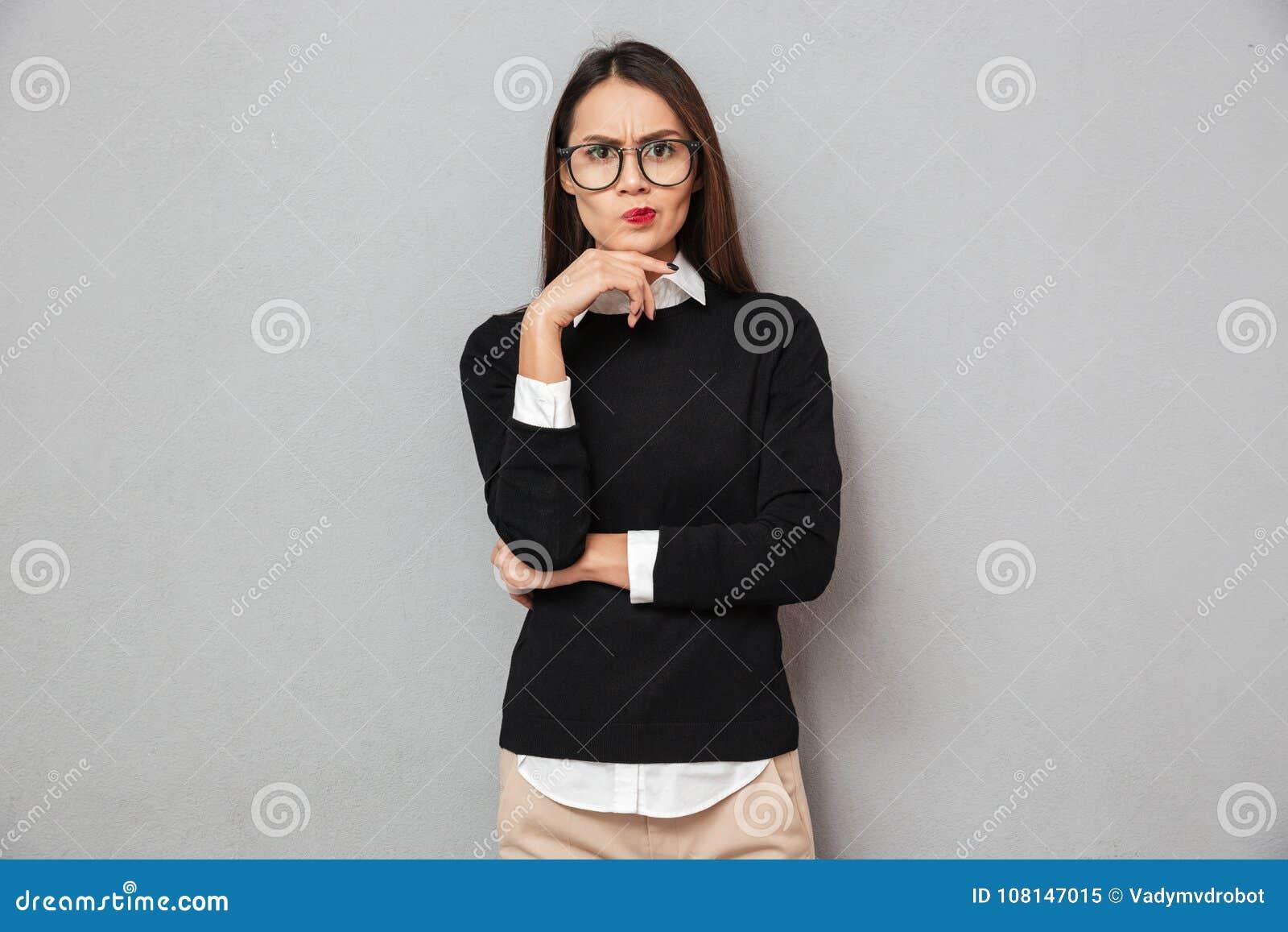 38a631e657 Mujer asiática pensativa seria en la ropa y las lentes del negocio que  miran la cámara sobre fondo gris