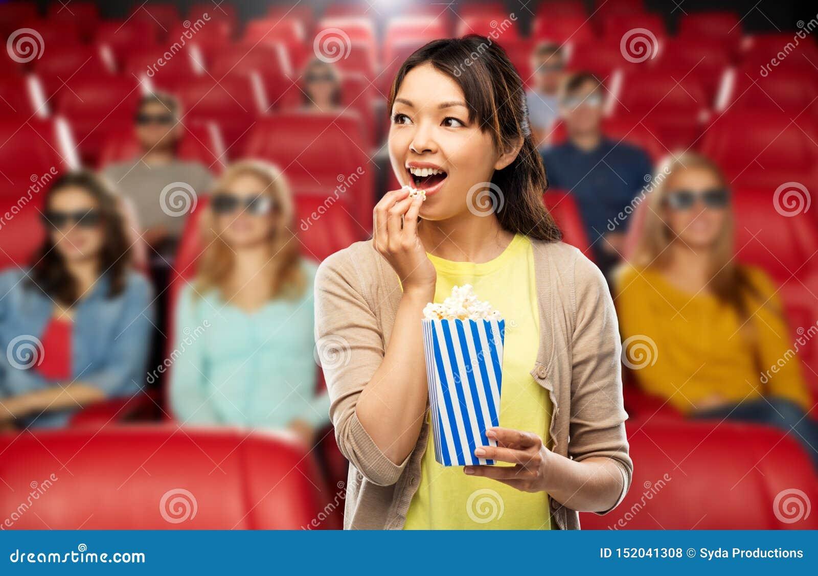 Mujer asiática que come las palomitas en el cine