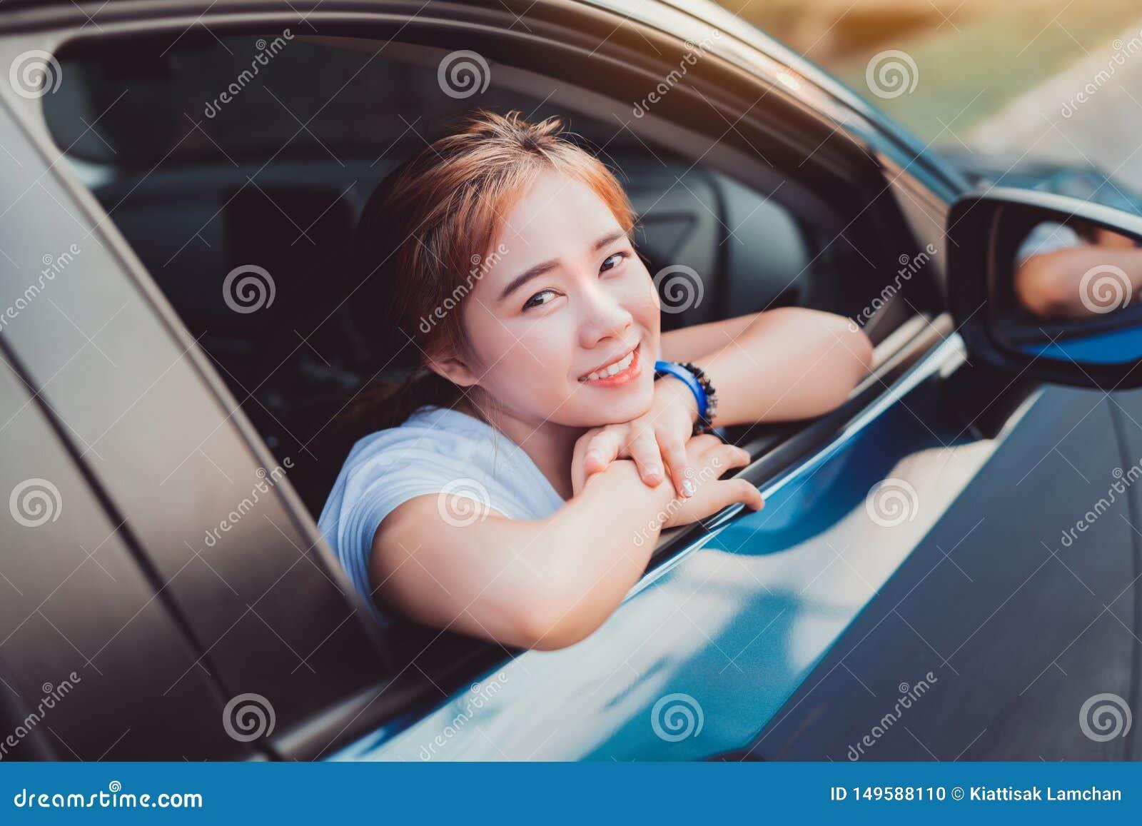 Mujer asiática que sonríe con el viaje en coche de la ventana trasera que conduce vacaciones de verano del viaje por carretera
