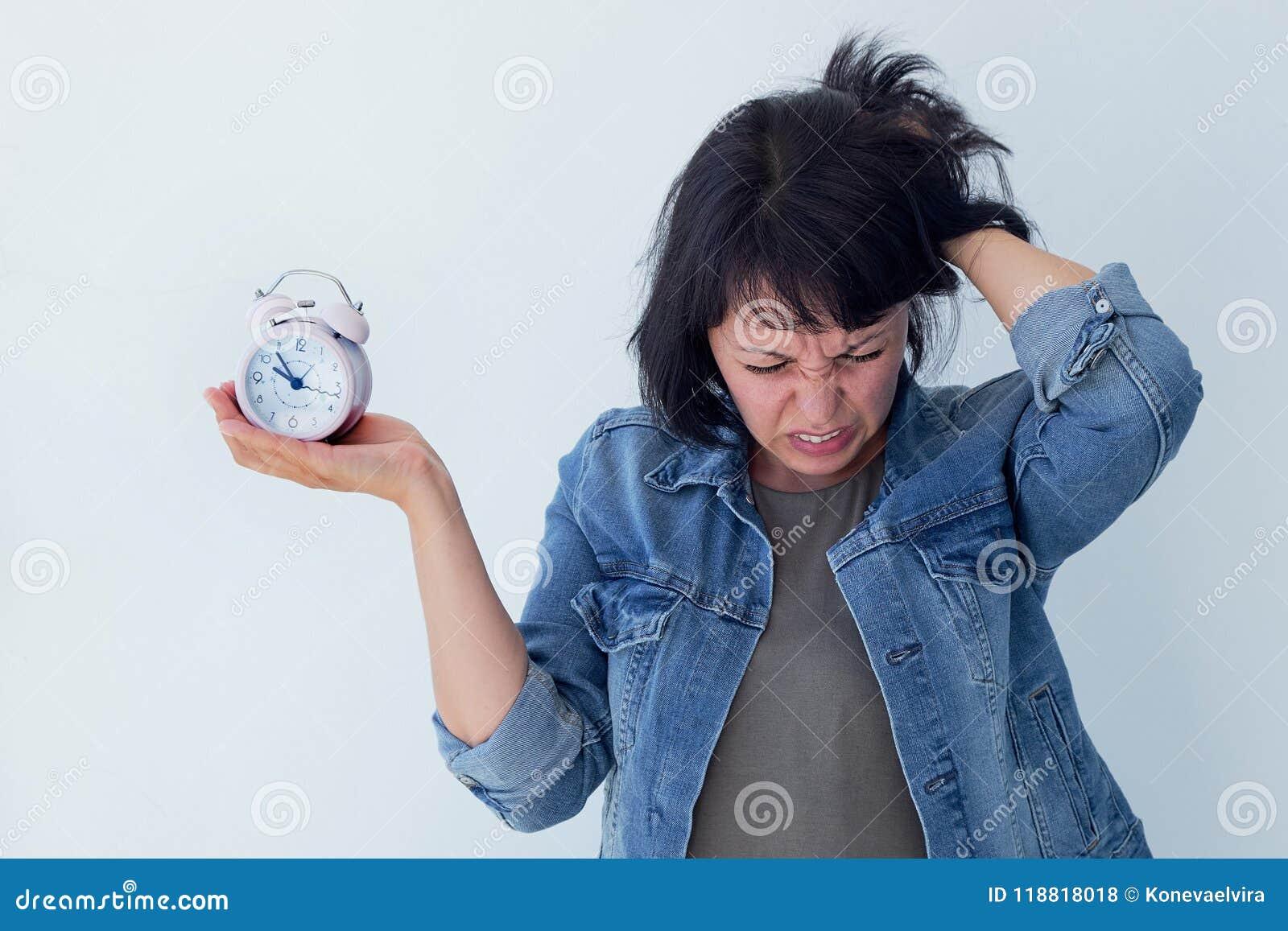 Mujer asiática que sostiene un despertador rosado en un fondo blanco El concepto de gestión de tiempo consiga el control de su vi