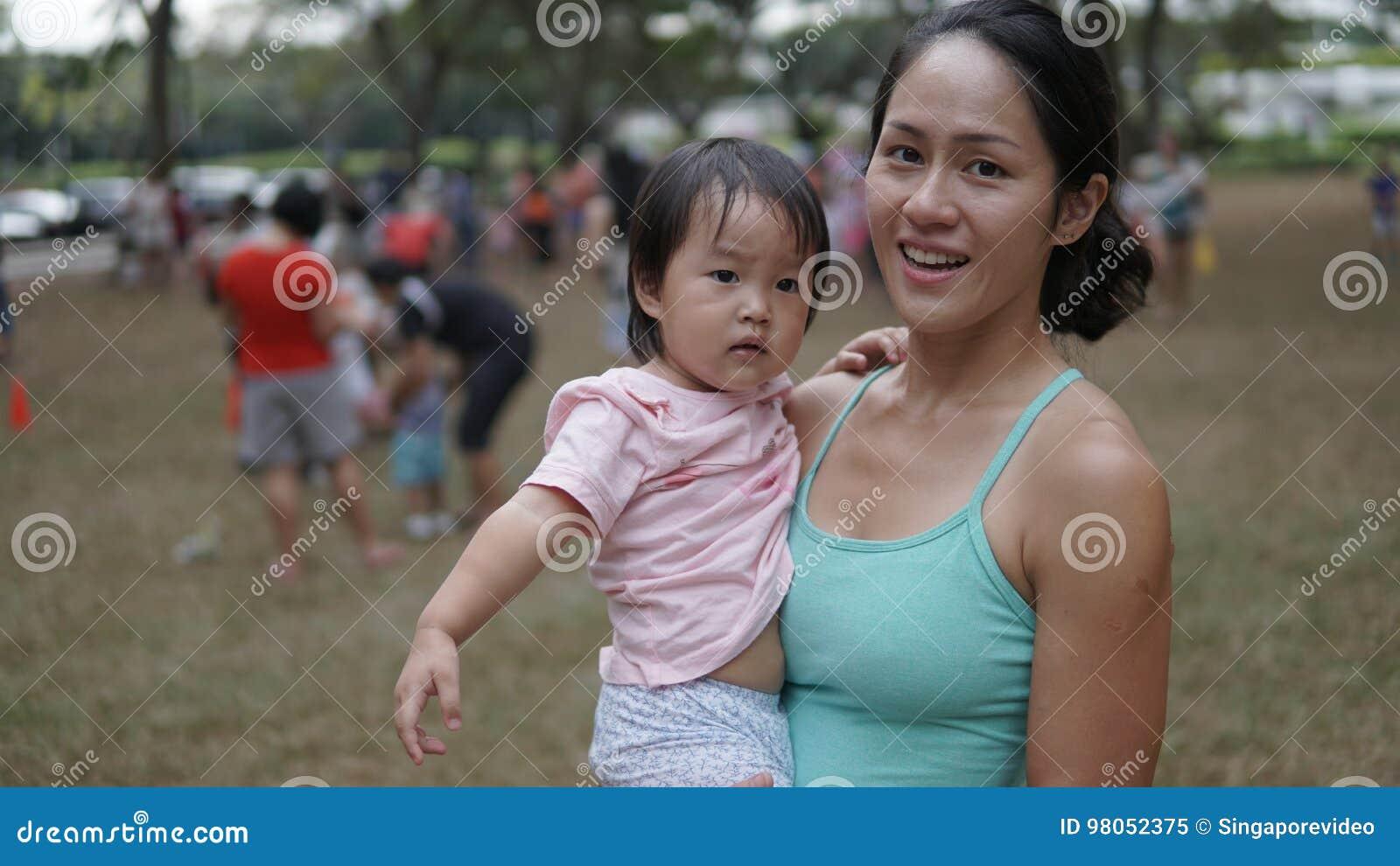 Mujer Asiatica Y Nino Que Participan En Los Juegos De La Familia Al