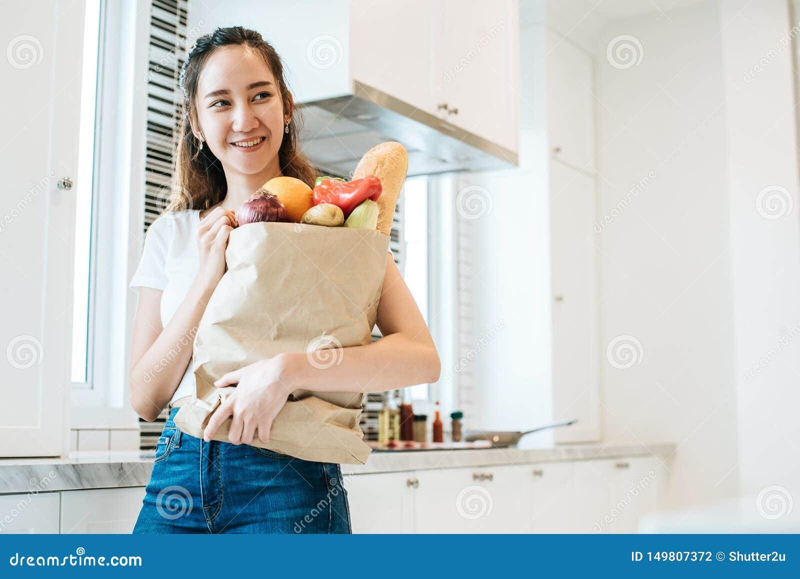 Mujer asi?tica de la belleza que lleva a cabo el un mont?n de ingredientes para cocinar despu?s de hacer compras en la gente del