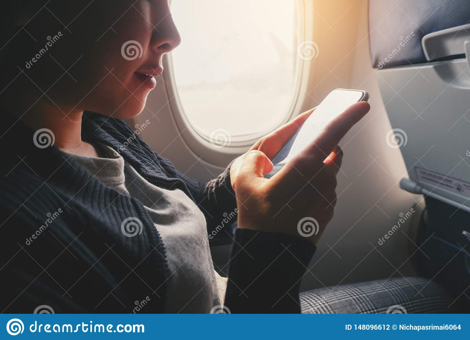 Mujer asi?tica tur?stica que se sienta cerca de ventana del aeroplano y que usa el tel?fono elegante durante vuelo