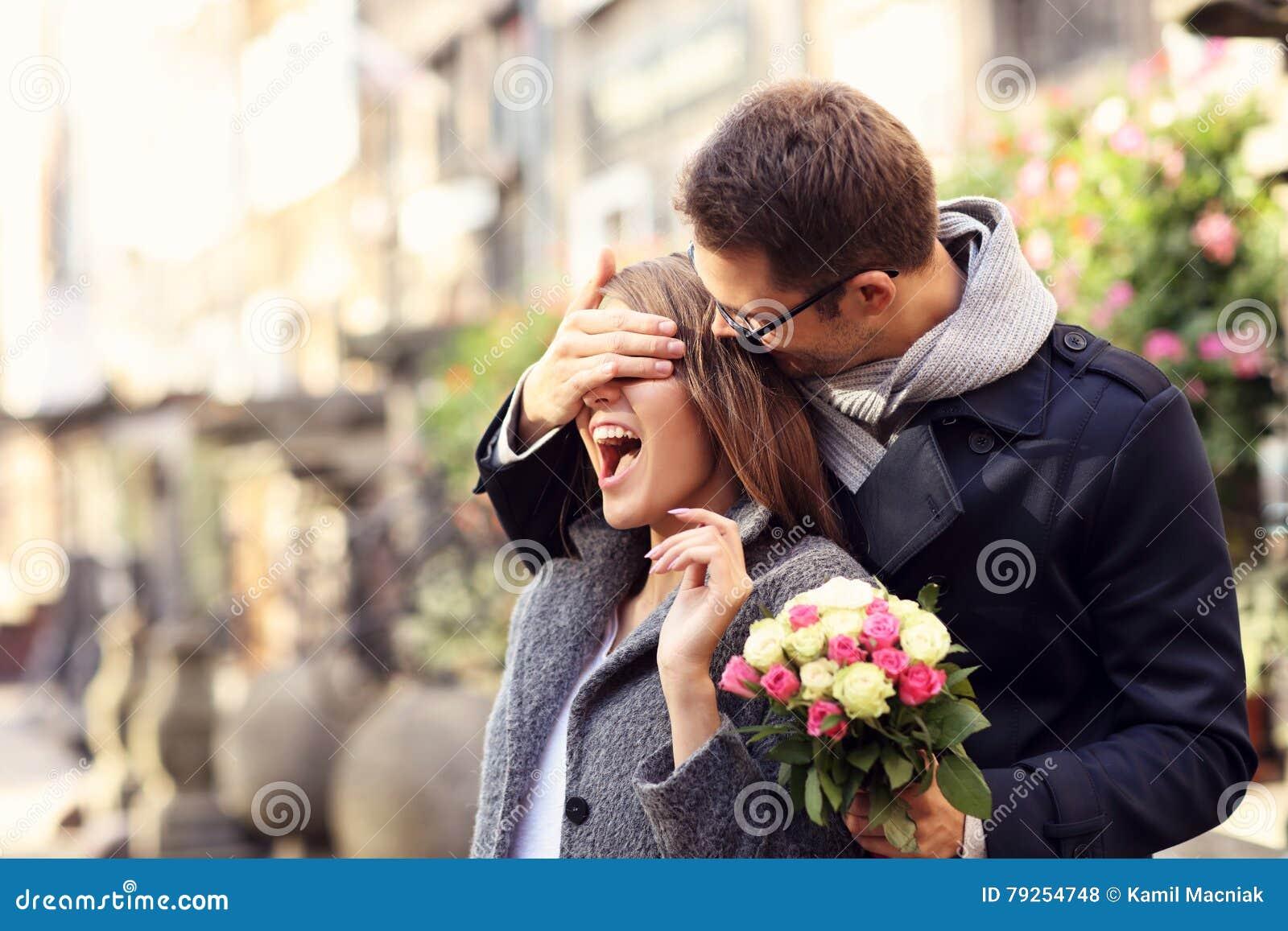 Mujer asombrosamente del hombre joven con las flores