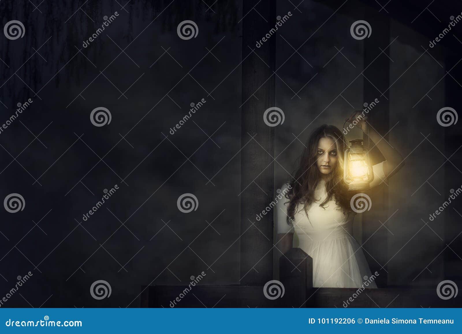 Mujer asustadiza con una linterna en escena de la noche