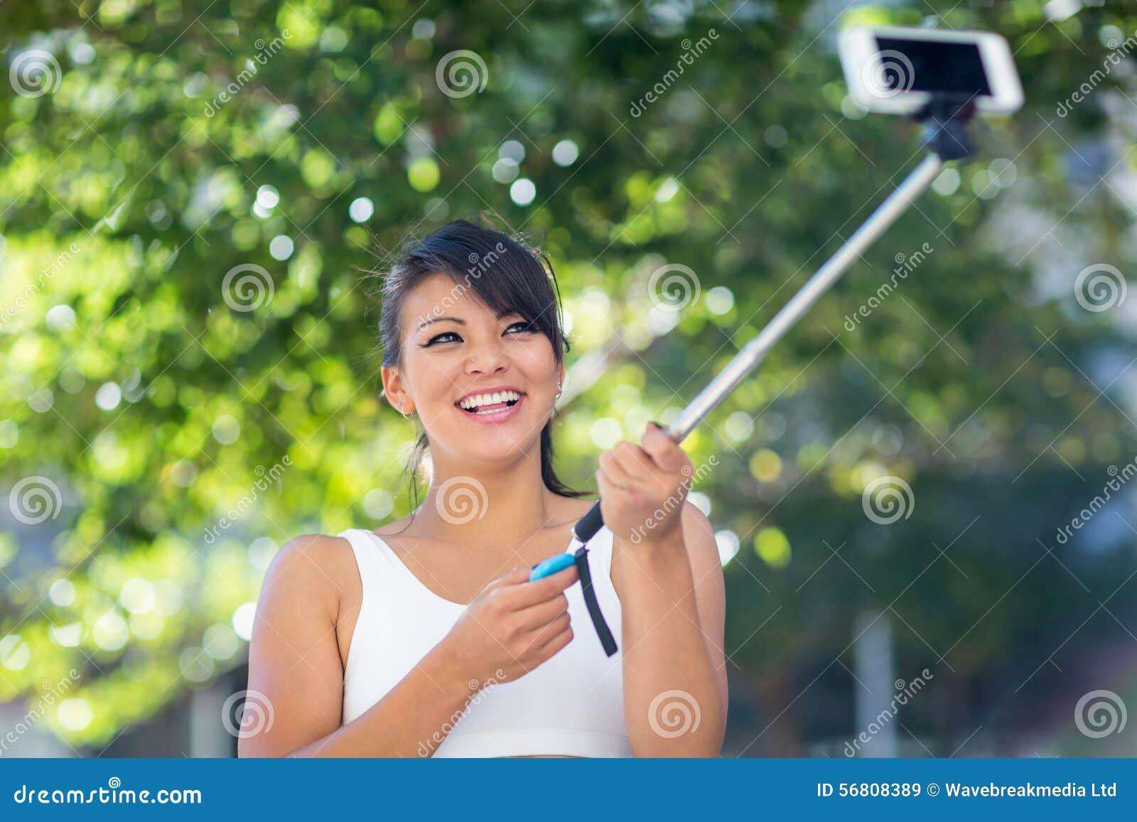 Mujer atlética sonriente que toma selfies con el selfiestick