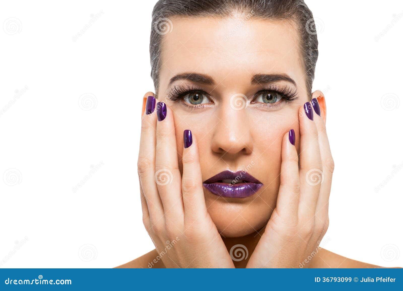 Mujer atractiva agraciada con los labios y los clavos púrpuras