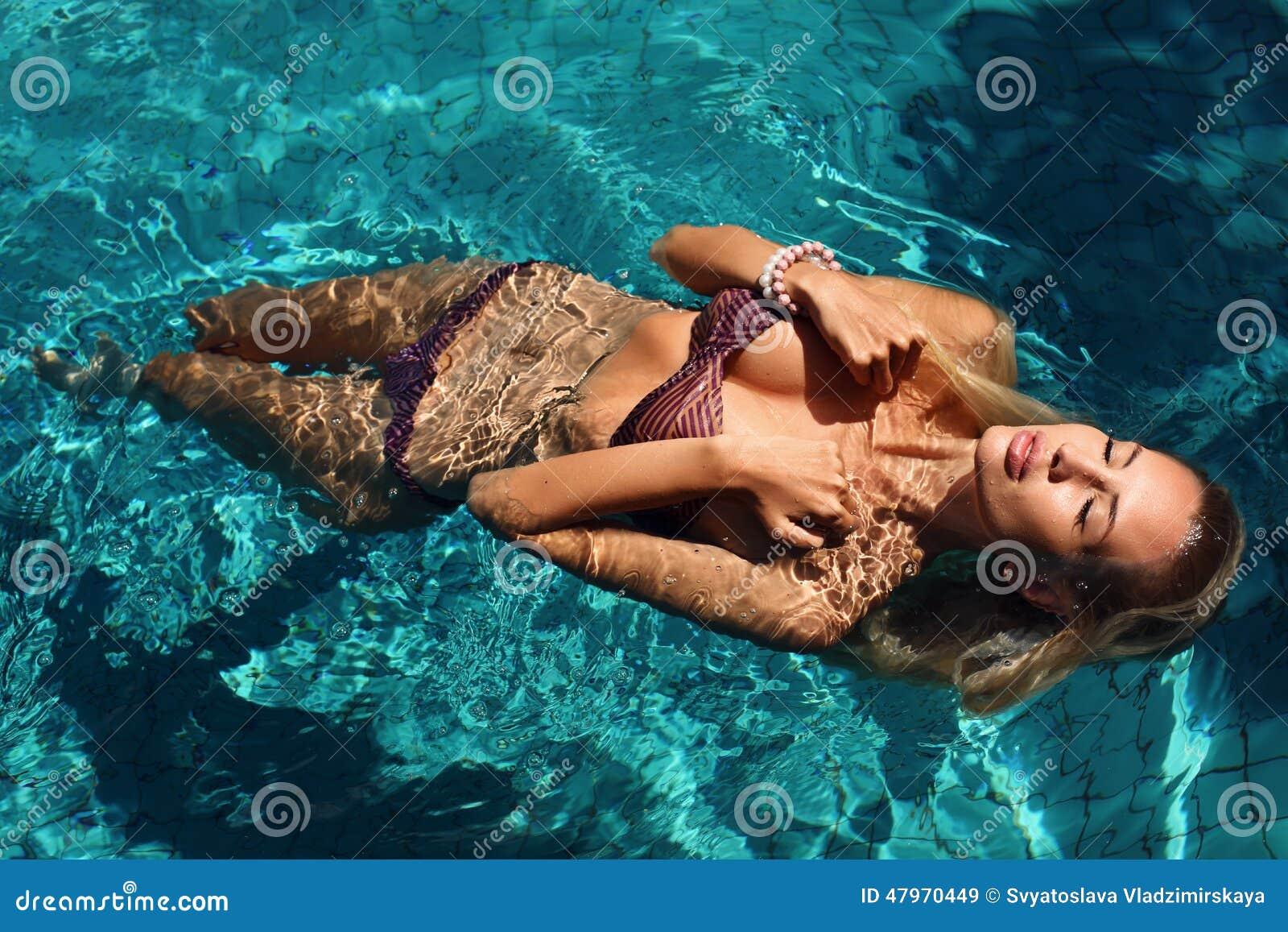 Mujer atractiva con el pelo rubio en el bikini que se relaja en piscina