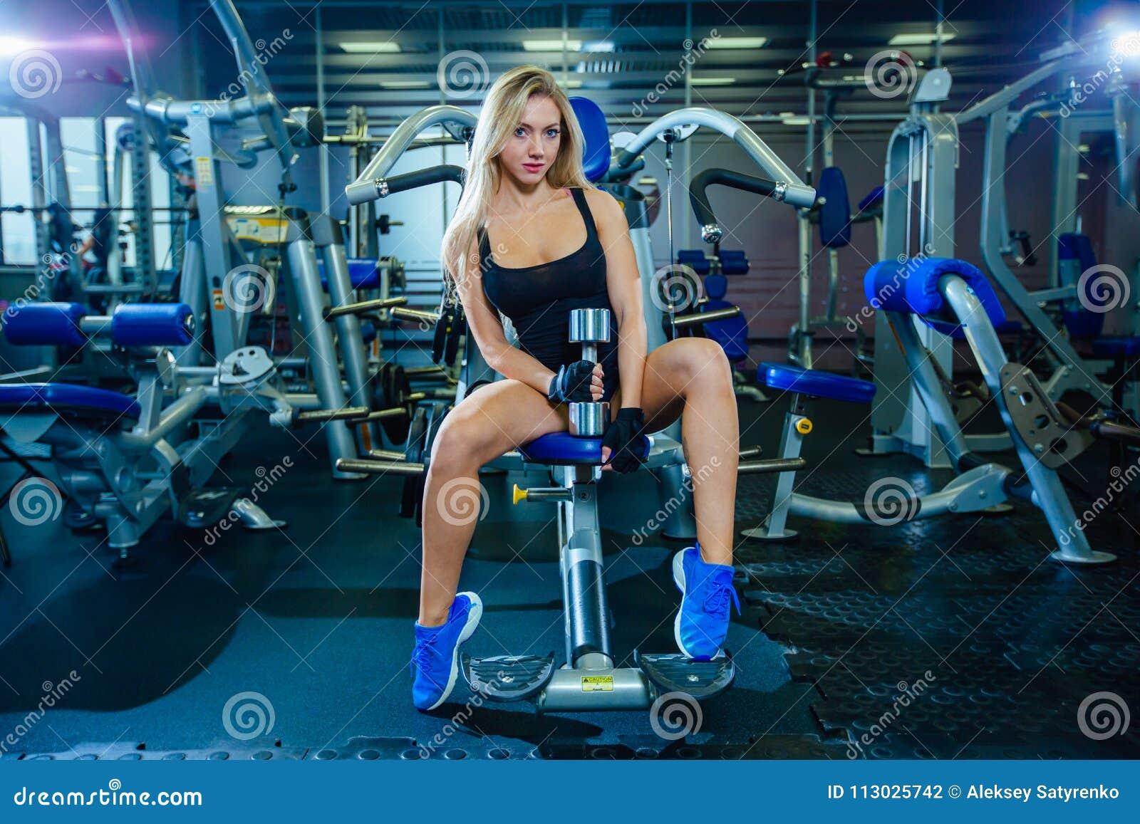 Mujer atractiva de la aptitud brutal con un muscular en el gimnasio Deportes y aptitud - concepto de forma de vida sana Mujer de