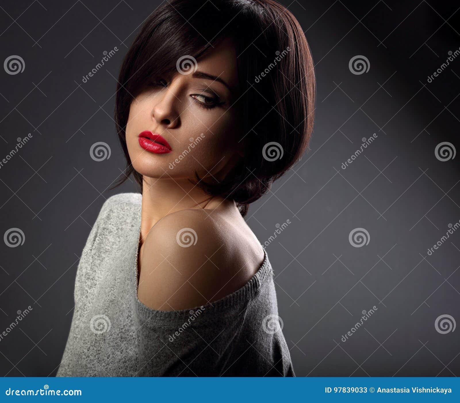 Mujer atractiva del maquillaje hermoso con rojo caliente del estilo de pelo corto y NU